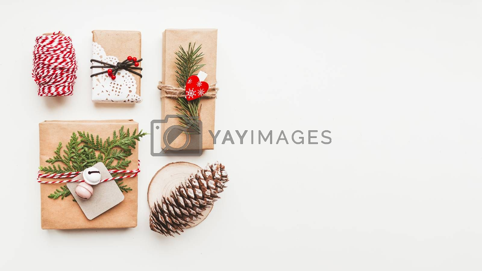 Christmas DIY presents wrapped in craft paper with fir tree twigs and red hearts. Top view on decorations on New Year gifts. Festive background. Winter holiday spirit. Banner with copy space.