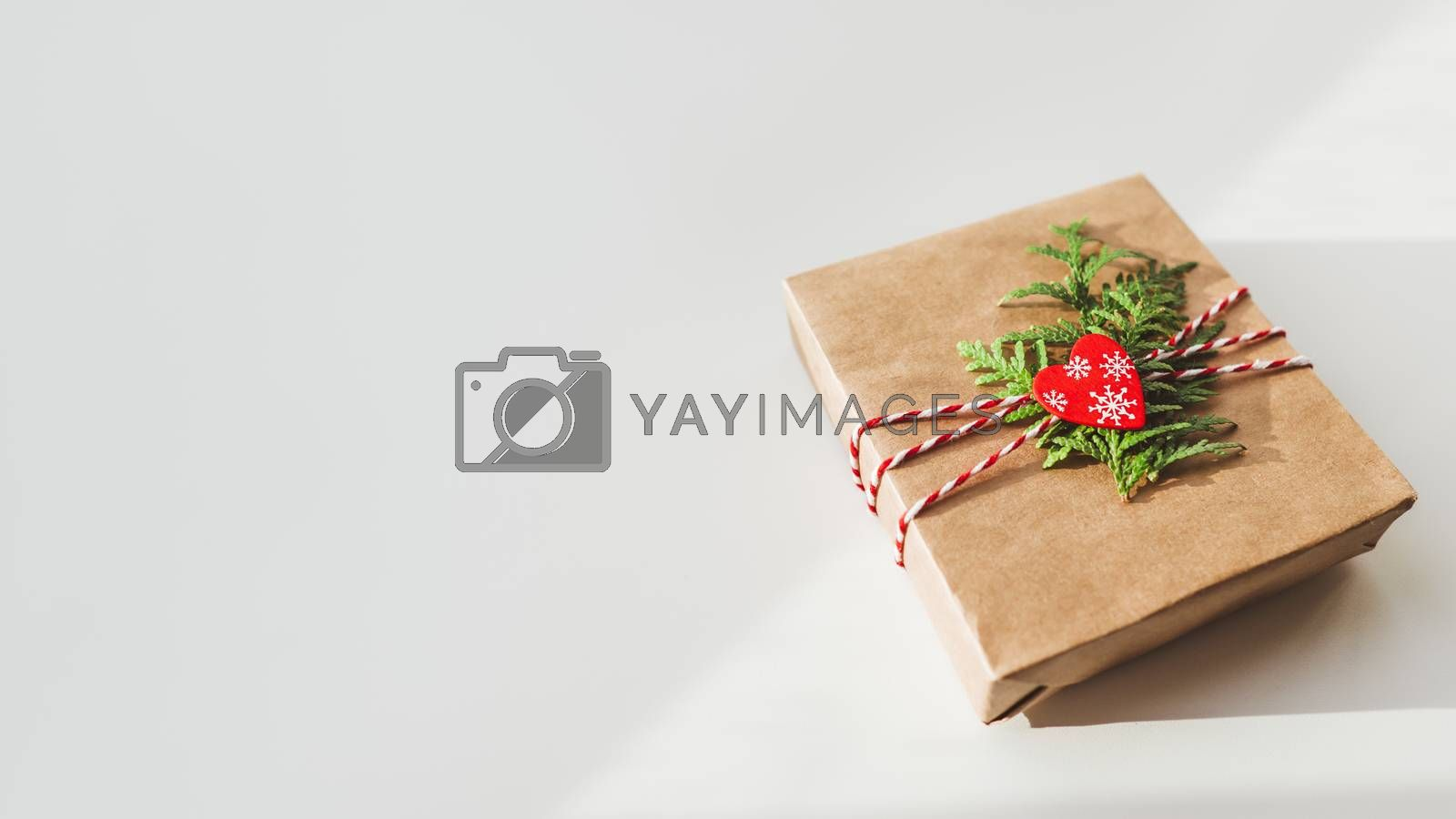 Christmas DIY presents wrapped in craft paper with fir tree branches and red heart. Decorations on New Year gifts. Festive background. Winter holiday spirit.