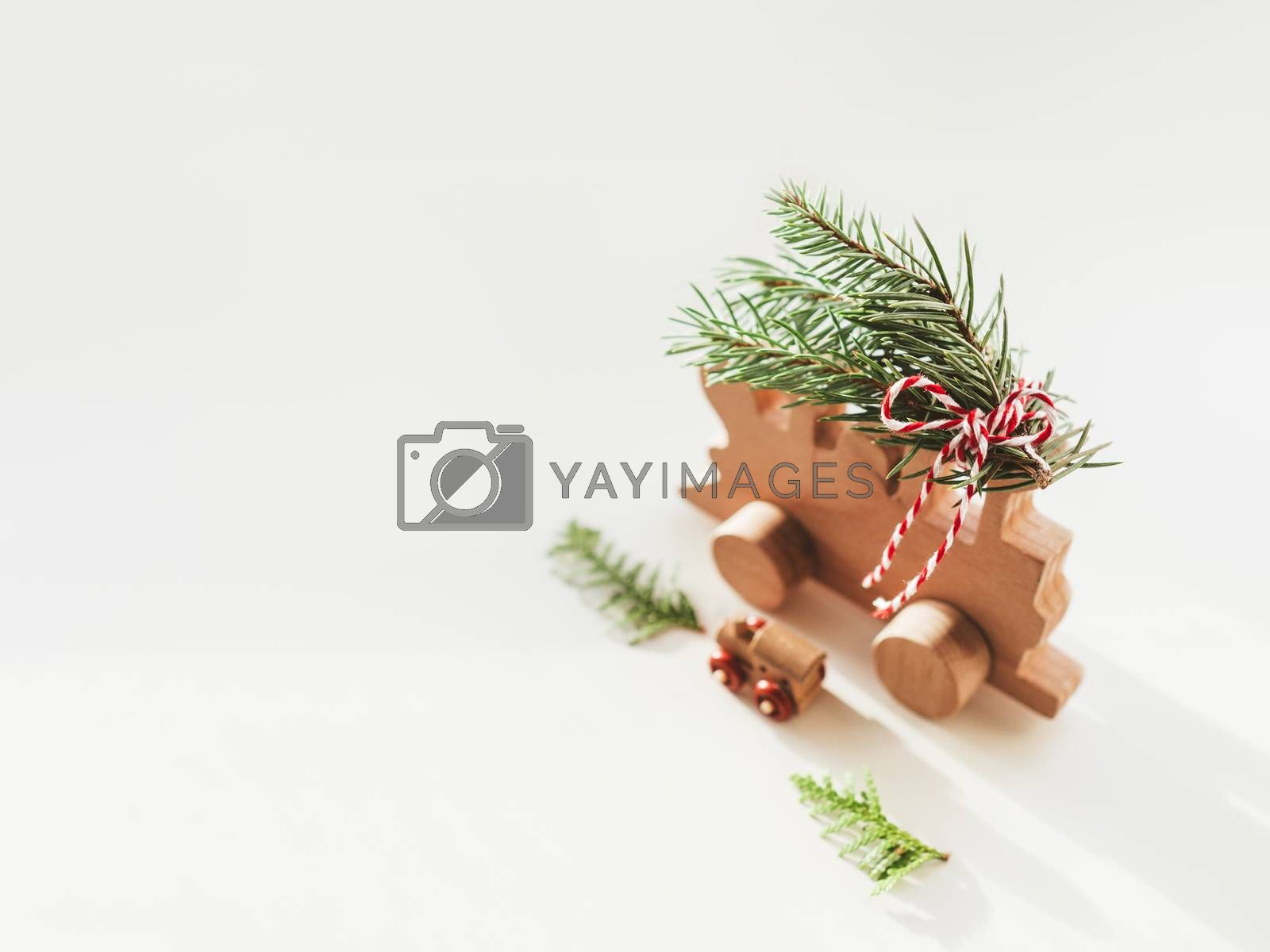 Two wooden trains with tied fir tree coniferous twigs. Dad and baby. Cute symbol of Christmas tree brought home for New Year celebration. Winter holiday spirit. Copy space.