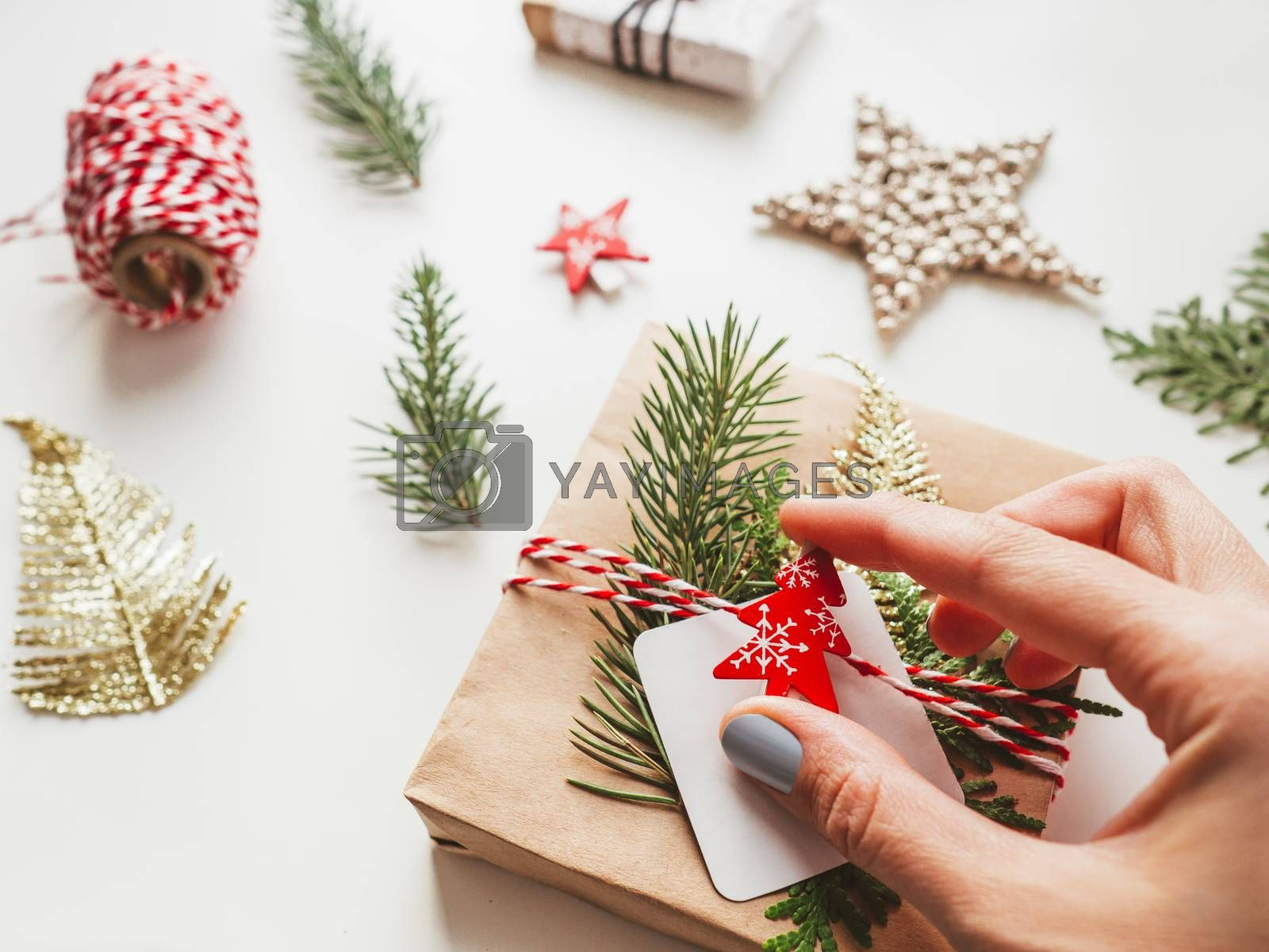 DIY presents wrapped in craft paper with fir tree twigs and red symbol of Christmas tree. Top view on decorations on New Year gifts. Festive background. Winter holiday spirit.