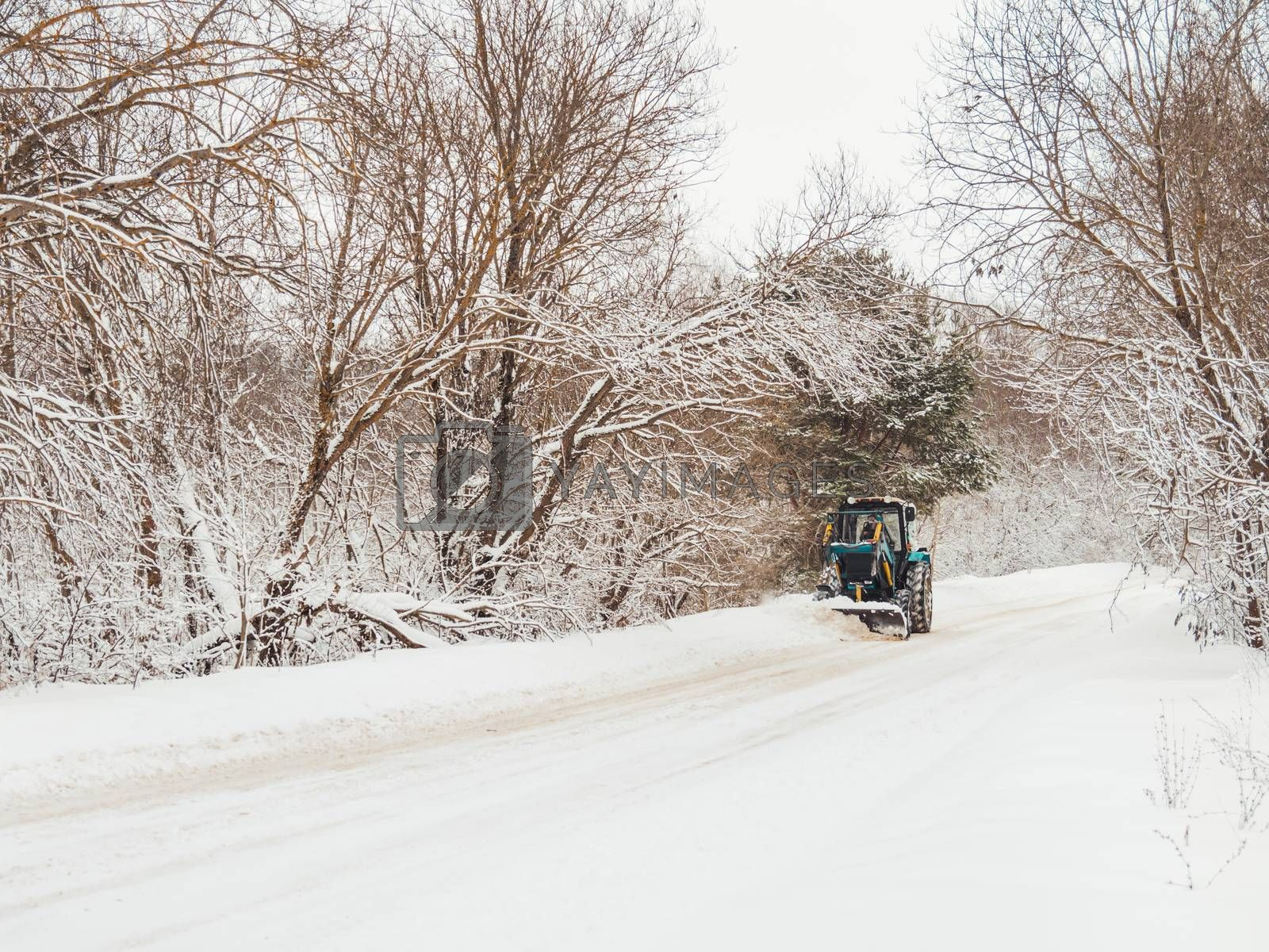 Snowplow clears rural road of snow debris after heavy snowstorm. Winter natural background with trees and country road under snow. Countryside landscape.