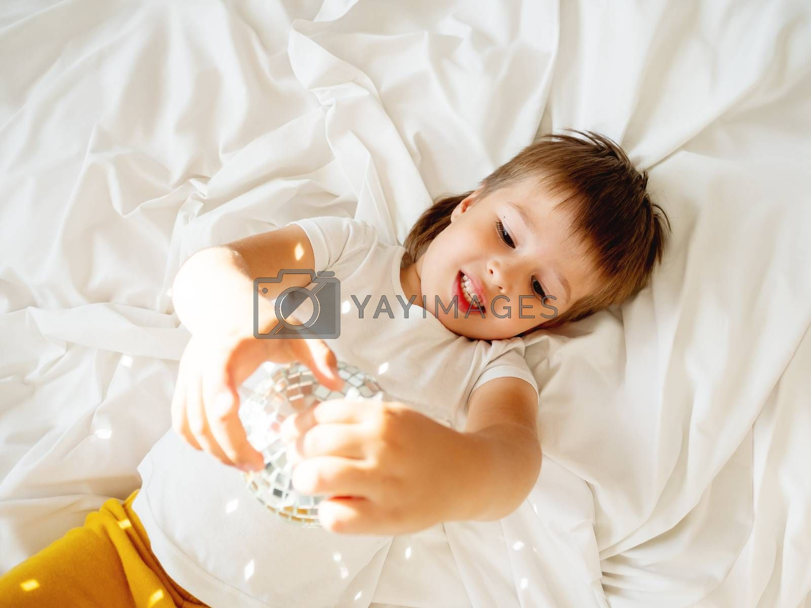 Little boy plays with sparkling mirror disco ball in bed and laughing happily. Joyful toddler. Playful child and sunny morning in cozy home.