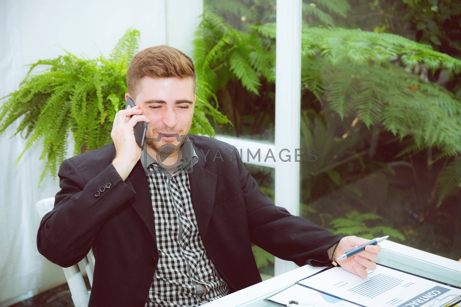 Businessman talking on smart mobile phone with document on desk with smiling, man call phone at office with professional, business and communication concept.