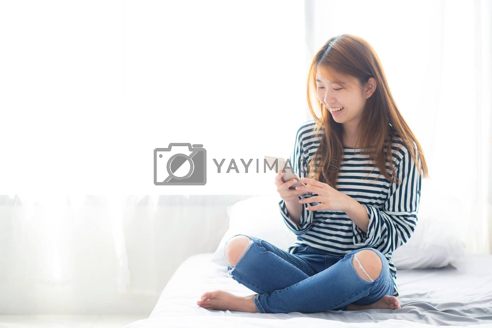 Beautiful young asian woman smiling sitting relax on the bed in the morning, girl using mobile smart phone talking enjoy, communication and social network concept.