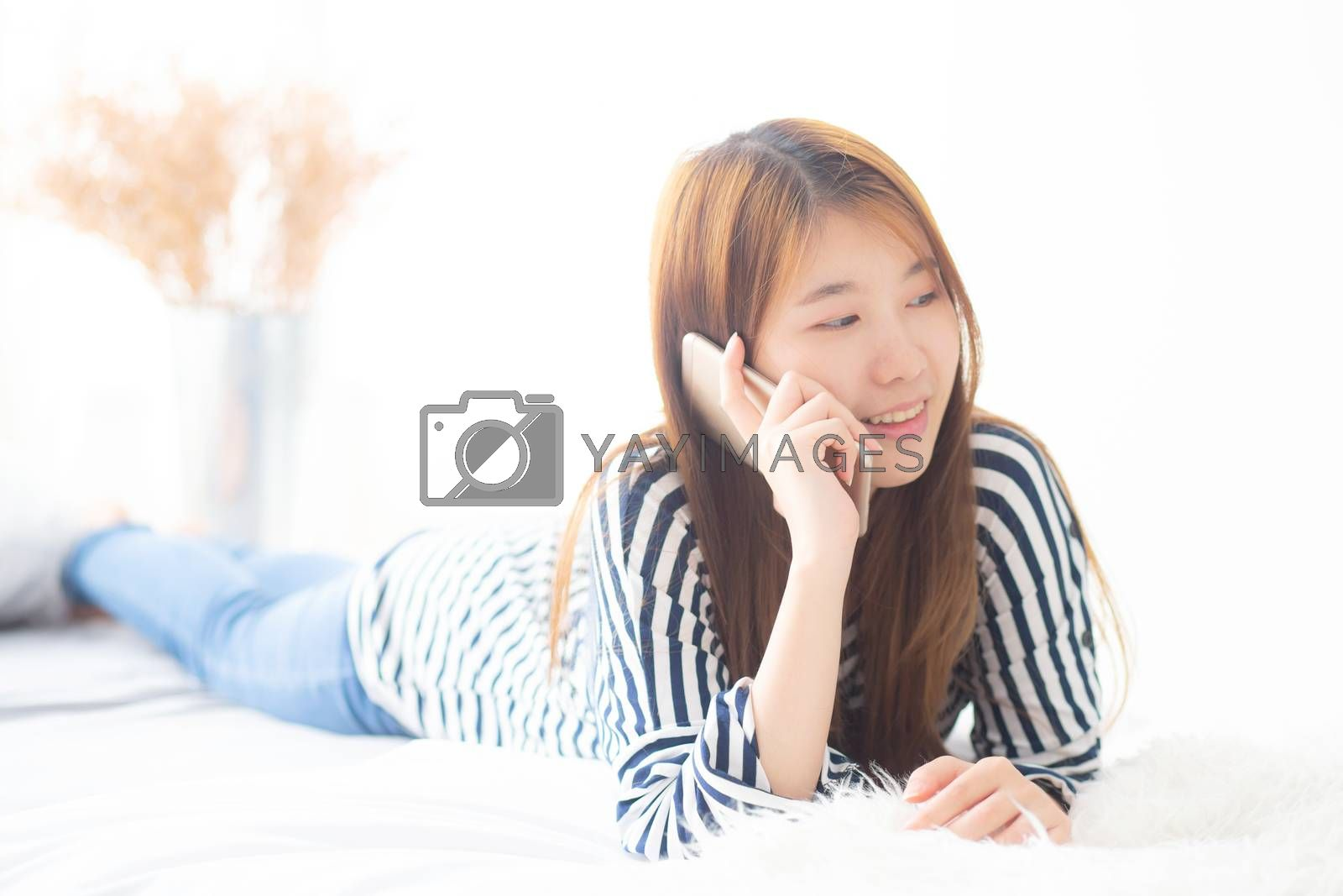 Beautiful young asian woman smiling lying relax on the bed in th by nnudoo