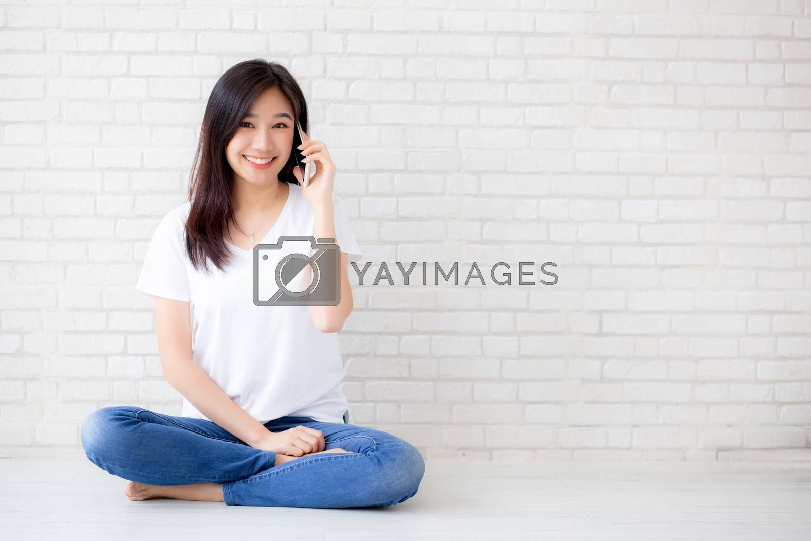 Beautiful of portrait young asian woman talk smart phone and smile sitting on cement concrete brick background, freelance female calling telephone, communication of mobile concept.