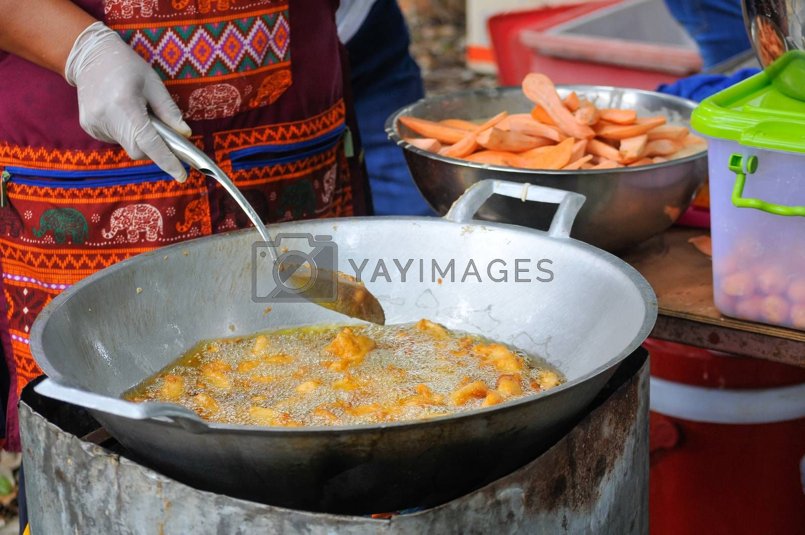 Sweet Potatoes being fried in Frying Pan with Heat Palm Oil, Fried Sweet Potatoes is Thailand Street Food or Thai Snack.