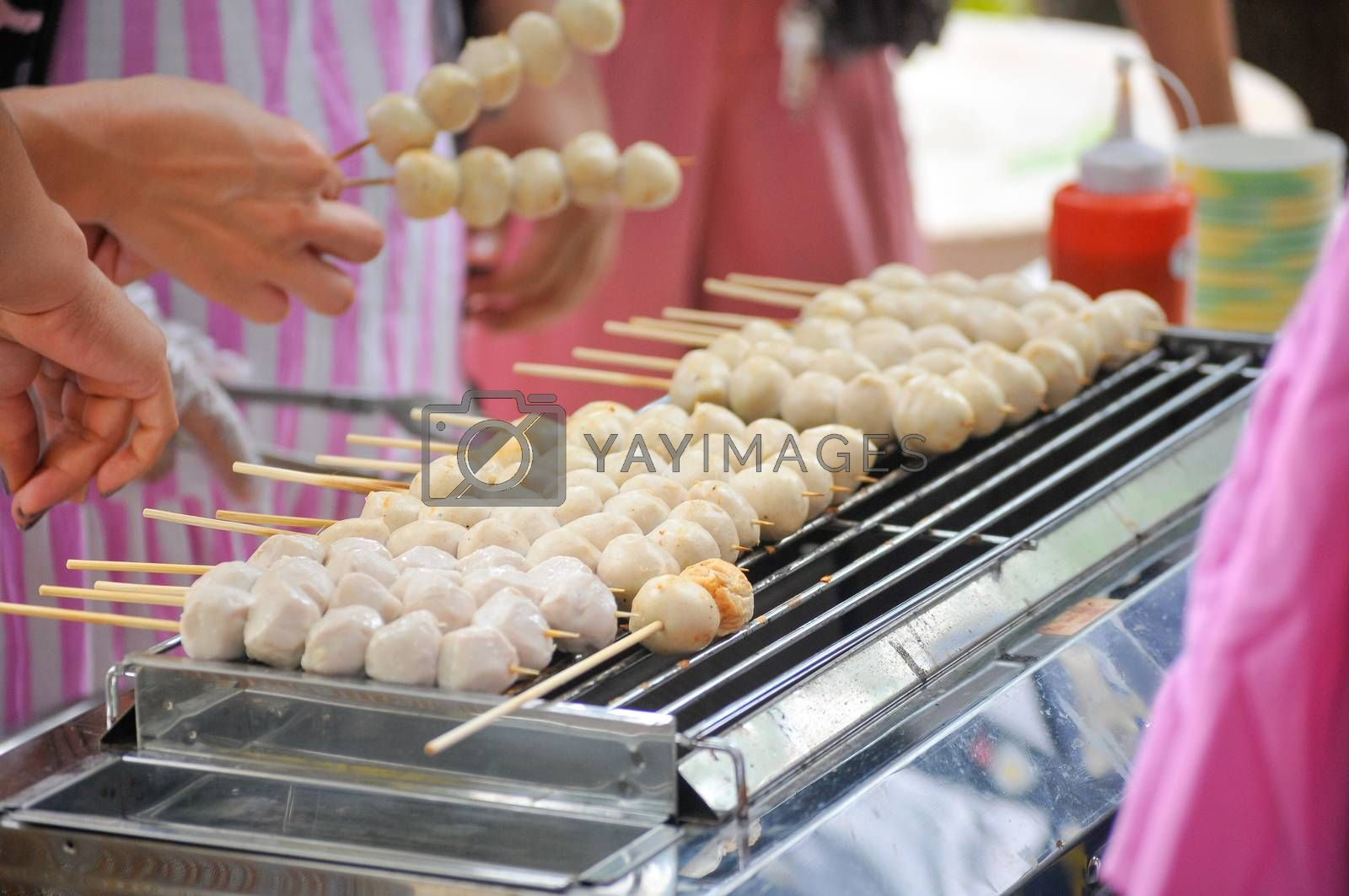 Close up grilled meatballs skewer bamboo with coriander topping , Beef balls tendon grilled street food market and fast food of Thailand.