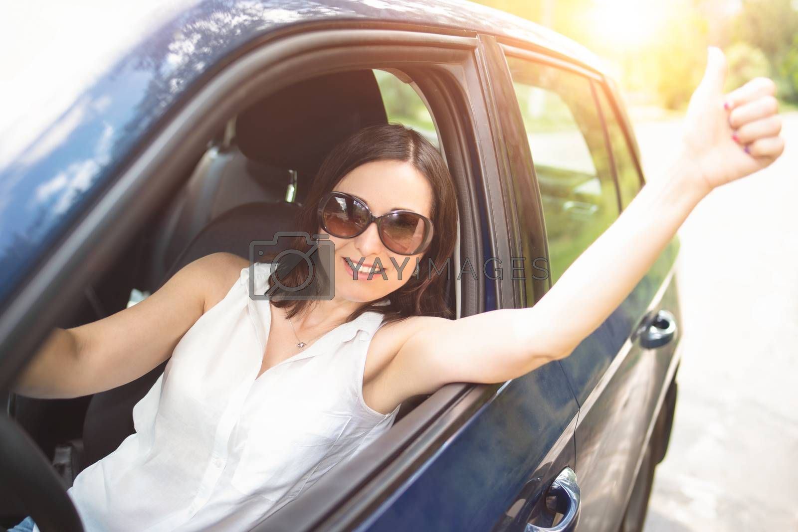 A smart looking middle-aged adult woman wearing sunglasses put her hand out the car window and raised her thumbs up.