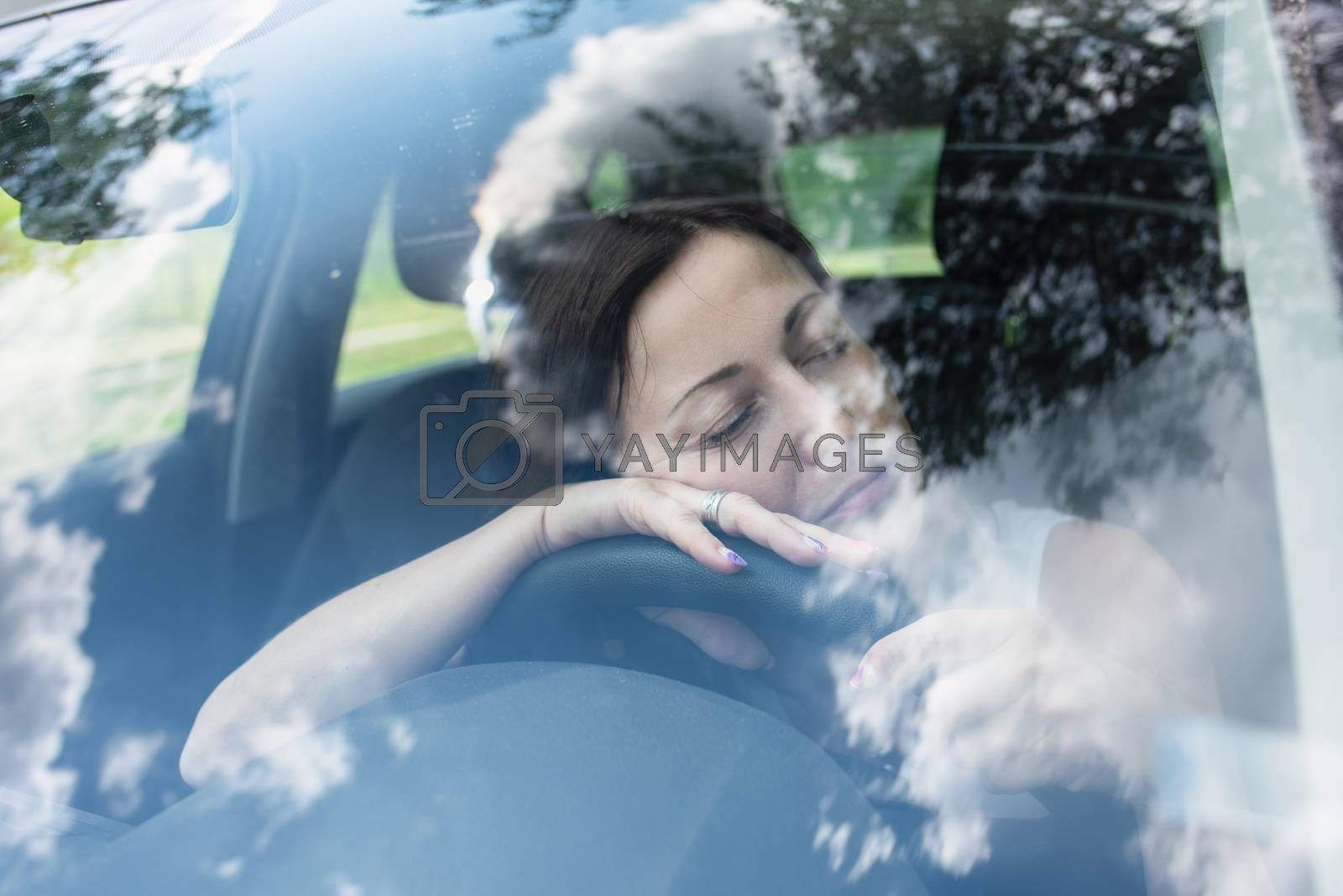 Young female driver at the wheel of her car, very tired, falling asleep while driving in a potentially dangerous situation - Road safety concept