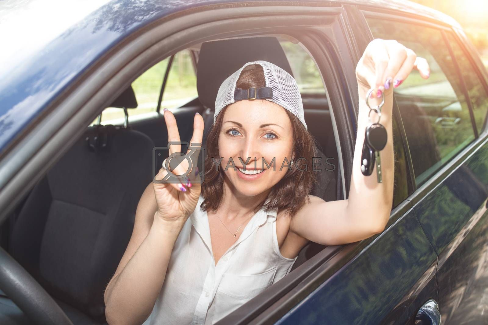 Beautiful woman in a hat holding keys to new bought car and smiling at camera in summer sunny day. Woman drives a car