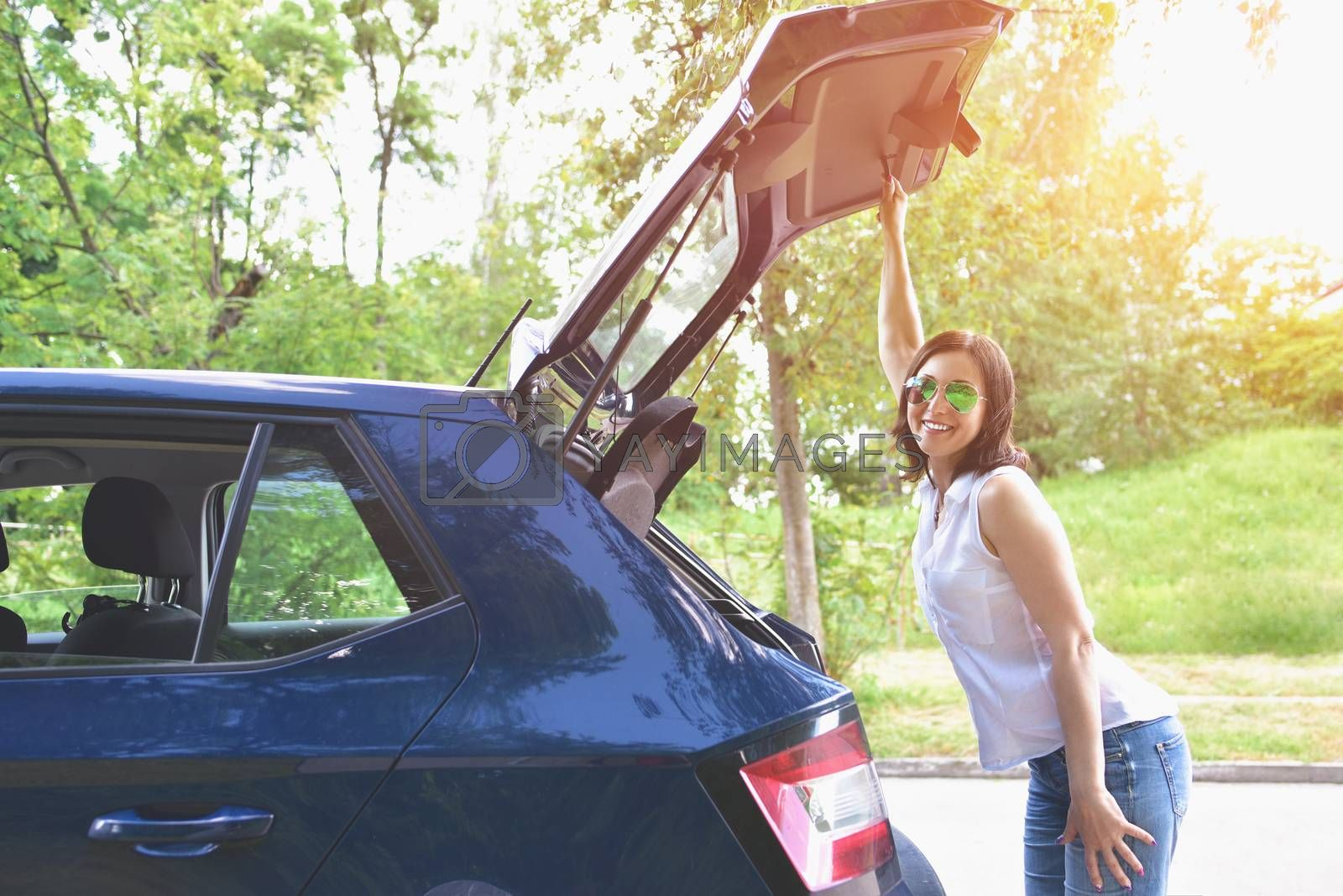 Smiling Caucasian woman in a white blouse and denim shorts putting her stuff bags into the car trunk