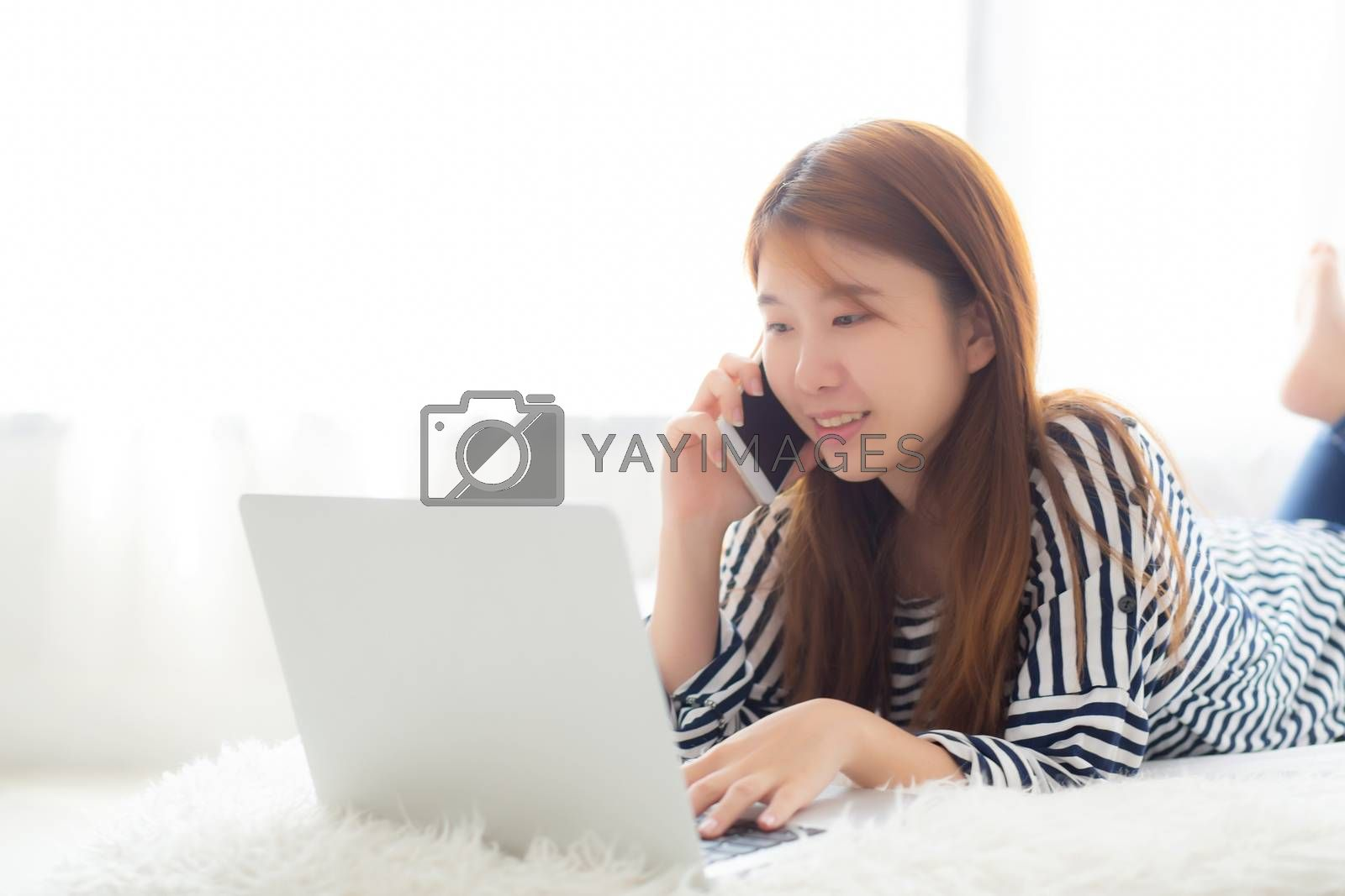 Beautiful asian young woman lying on bed using laptop and talking mobile smart phone at bedroom for leisure and relax, freelance with girl working notebook, communication concept.