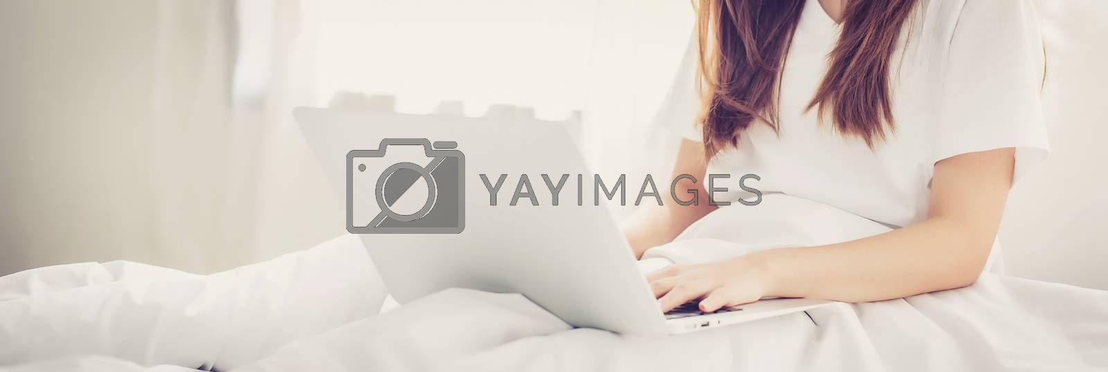 Banner website beautiful asian young woman setting on bed using laptop computer at bedroom for leisure and relax, freelance with girl working notebook, communication and lifestyle concept.