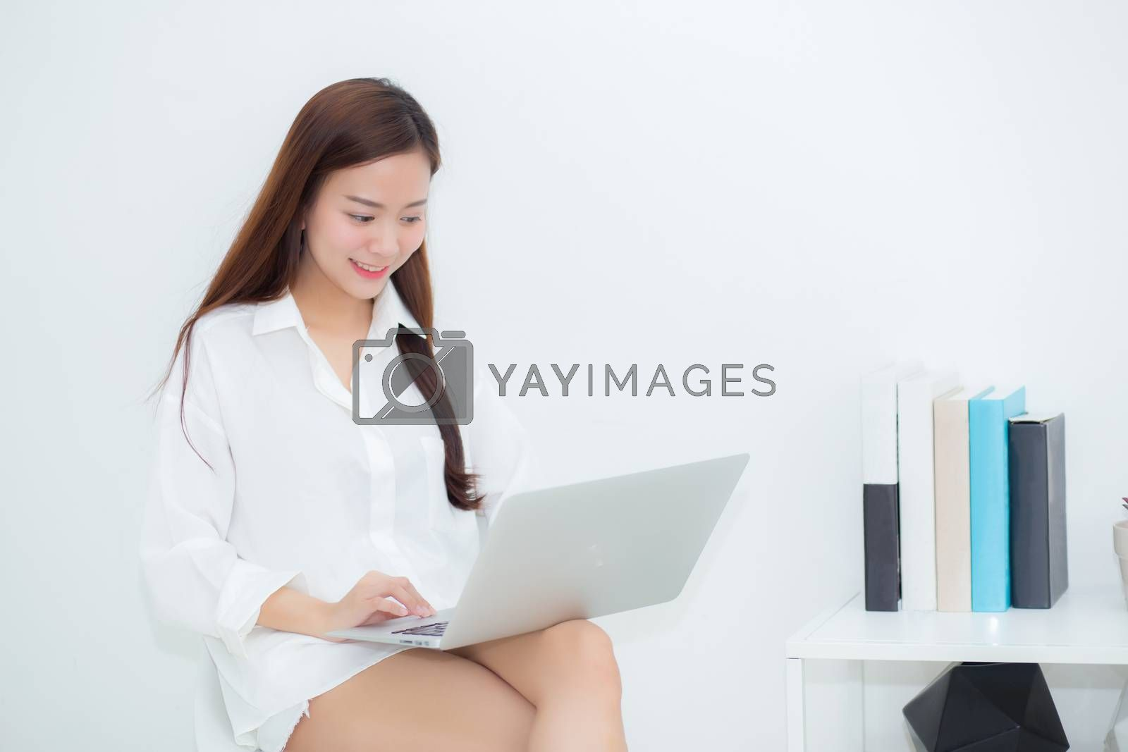 Beautiful young asian woman using laptop for leisure on sofa, gi by nnudoo