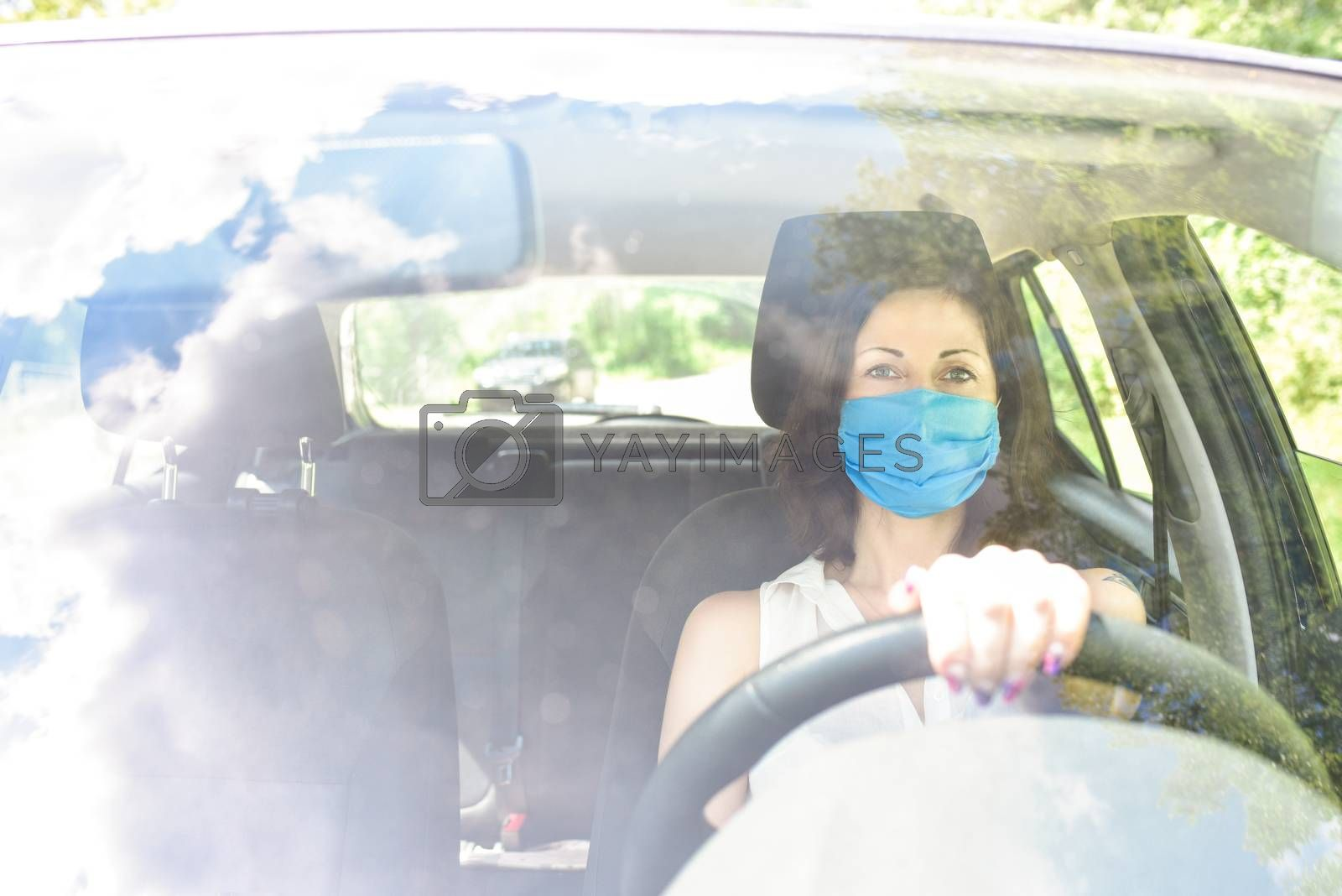 Beautiful young cheerful women with protective surgical mask looking at camera