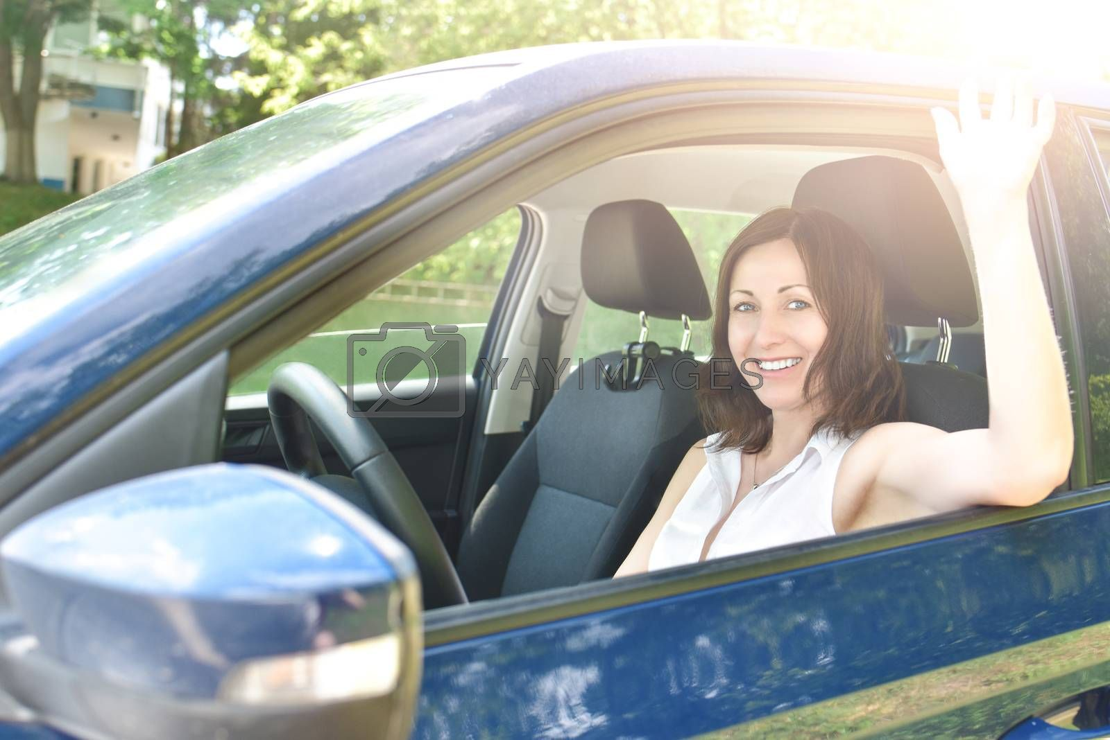 say hello, Beautiful happy adult woman sits in the car and waving his hand in greeting