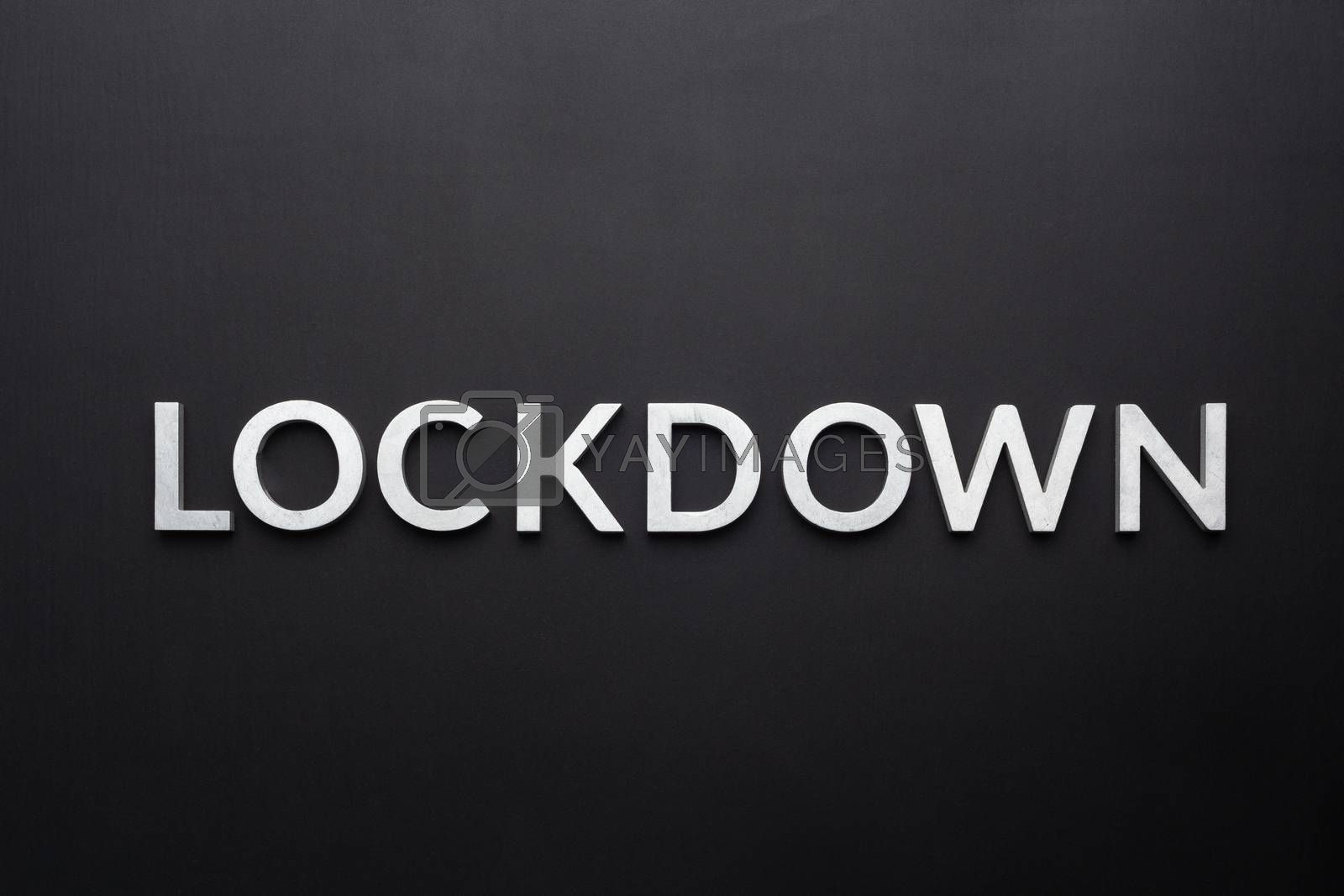 the word lockdown laid with silver metal letters on flat black background in directly above perspective.