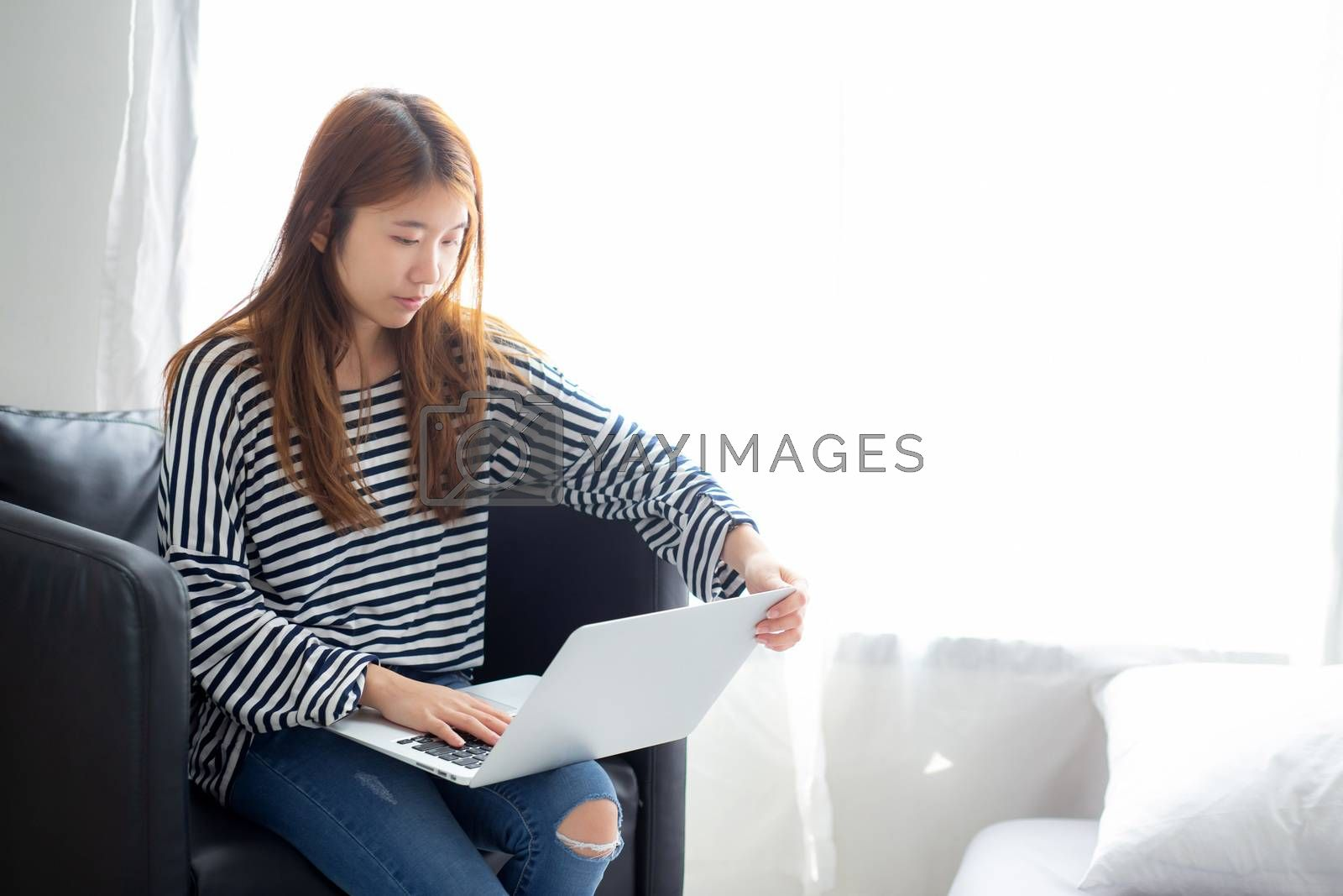 Beautiful of portrait young asian woman using laptop computer  for leisure on chair at living room, girl working online with notebook freelance, communication business concept.