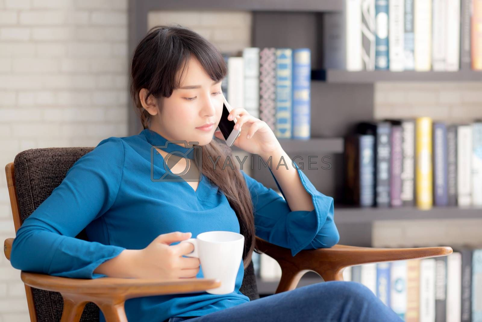 Beautiful portrait young asian woman smiling using mobile smart phone talking enjoy and drink coffee with relax, girl sitting on chair, communication concept.