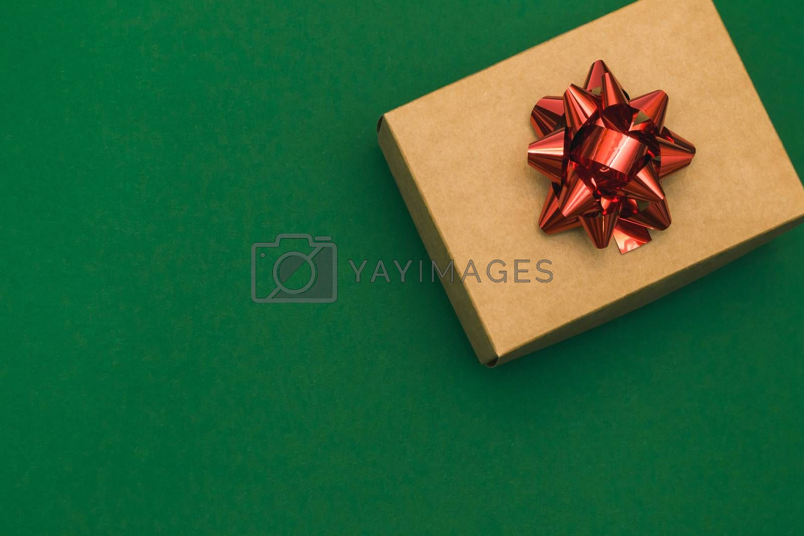 Christmas border with craft gift box and red bow on green background. Winter vacation. Postcard Happy New Year. Place for text. Top view, flat lay. Christmas. Template, banner.