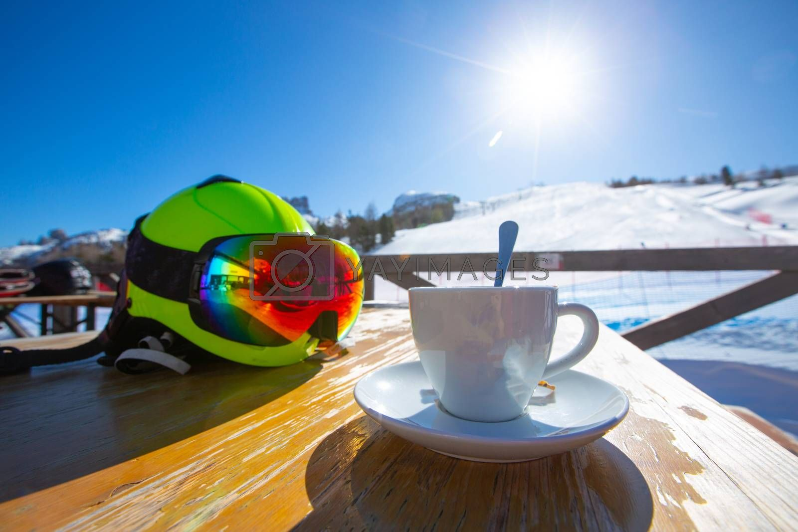 Cup of Cappuccino coffee on table in cafe at ski resort in Italy Dolomites alps
