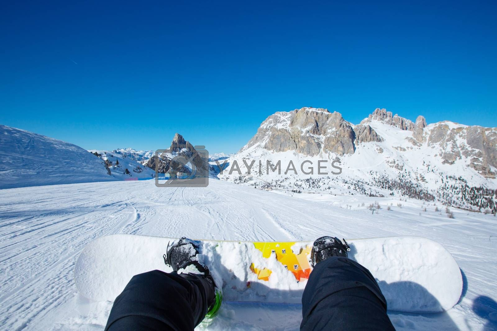 Snowboarder sitting on ski slope at resort in Dolomites Italian Alps view on legs and snowboard