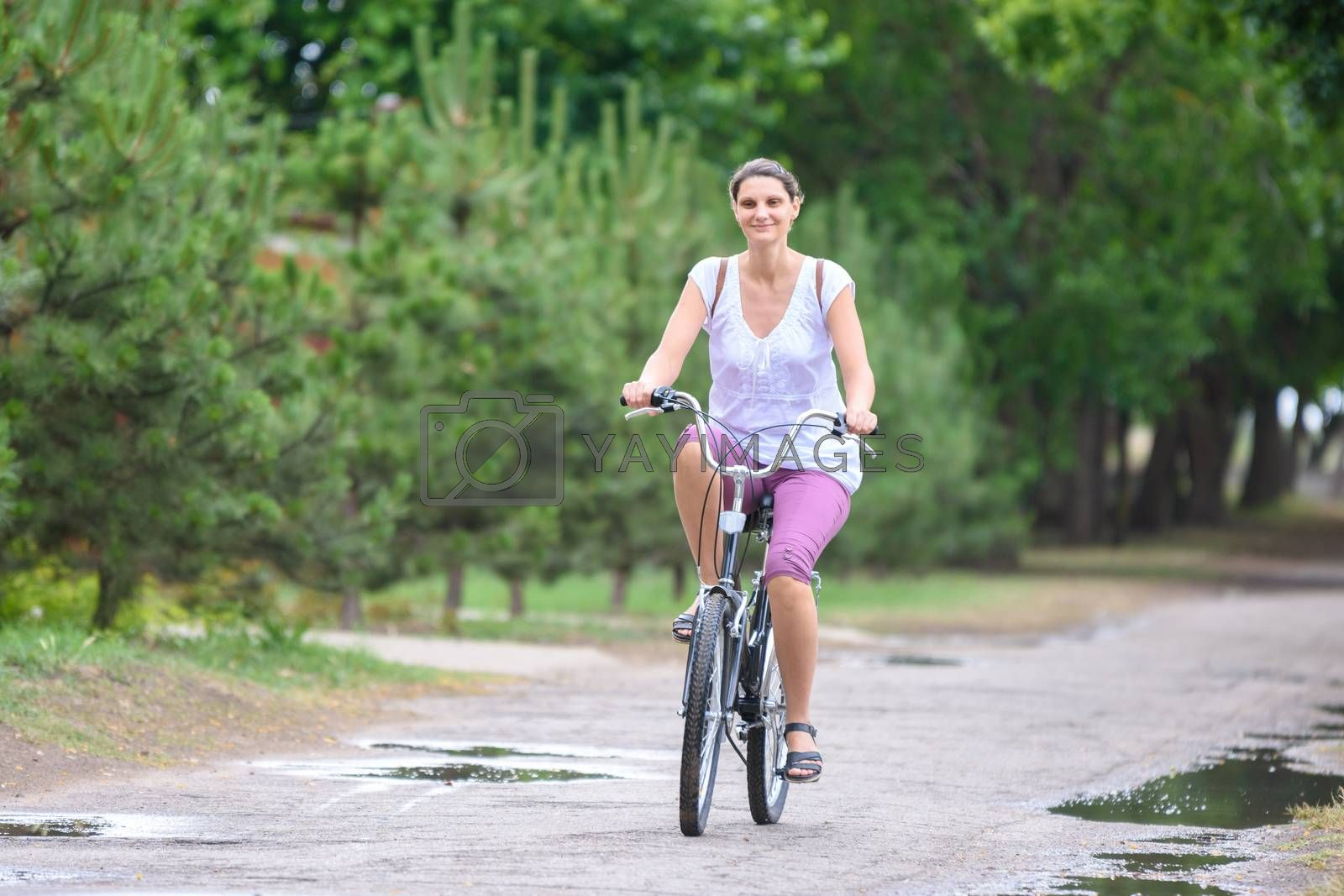 Girl riding a bicycle on a rainy warm summer morning