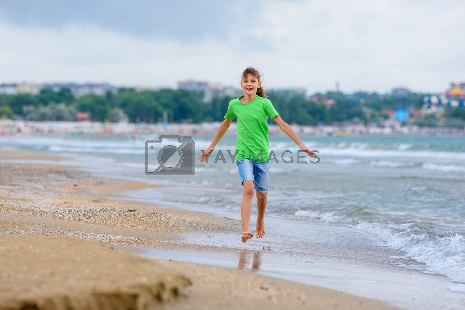 The girl runs happily along the sea coast