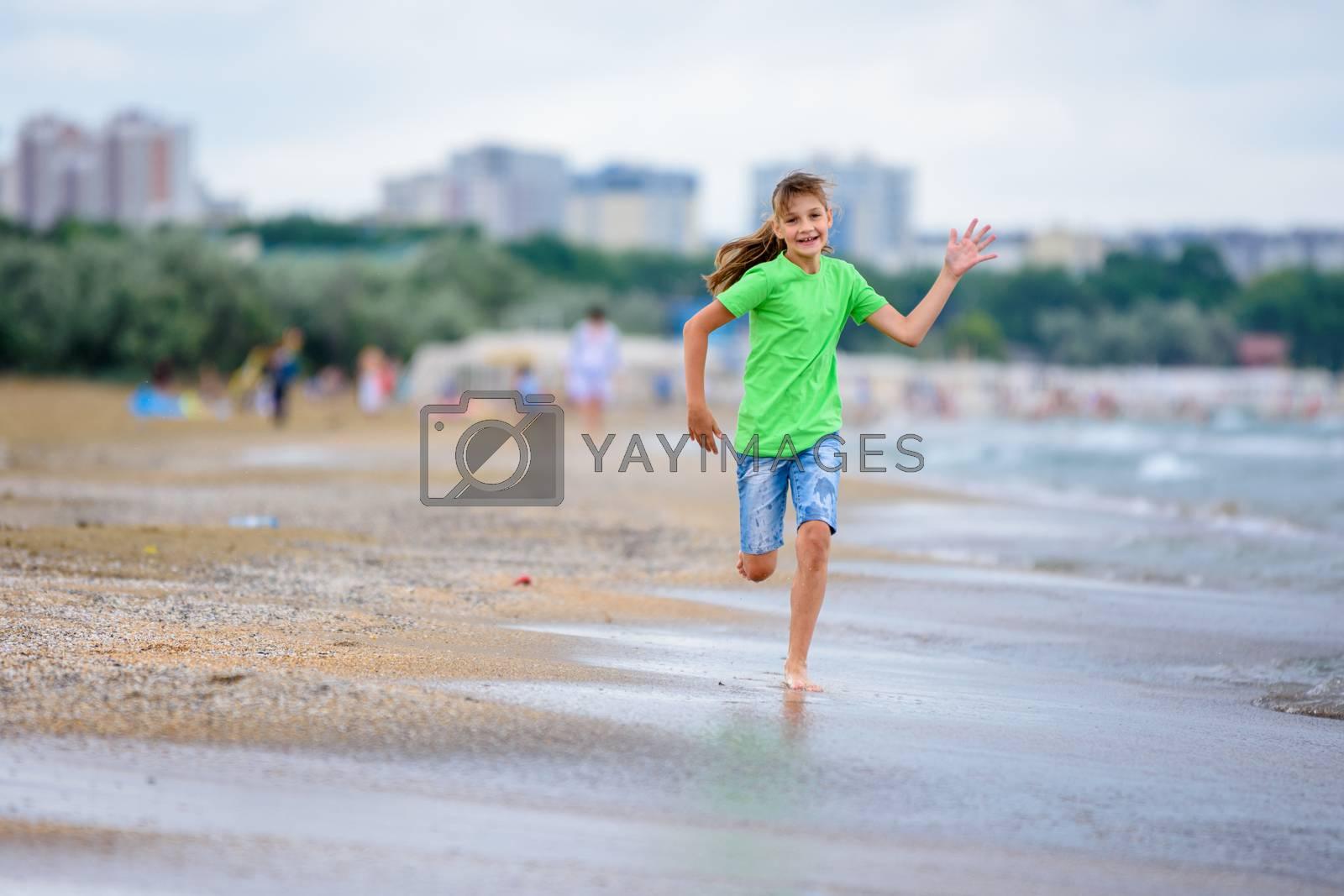A girl of ten runs joyfully along the seashore