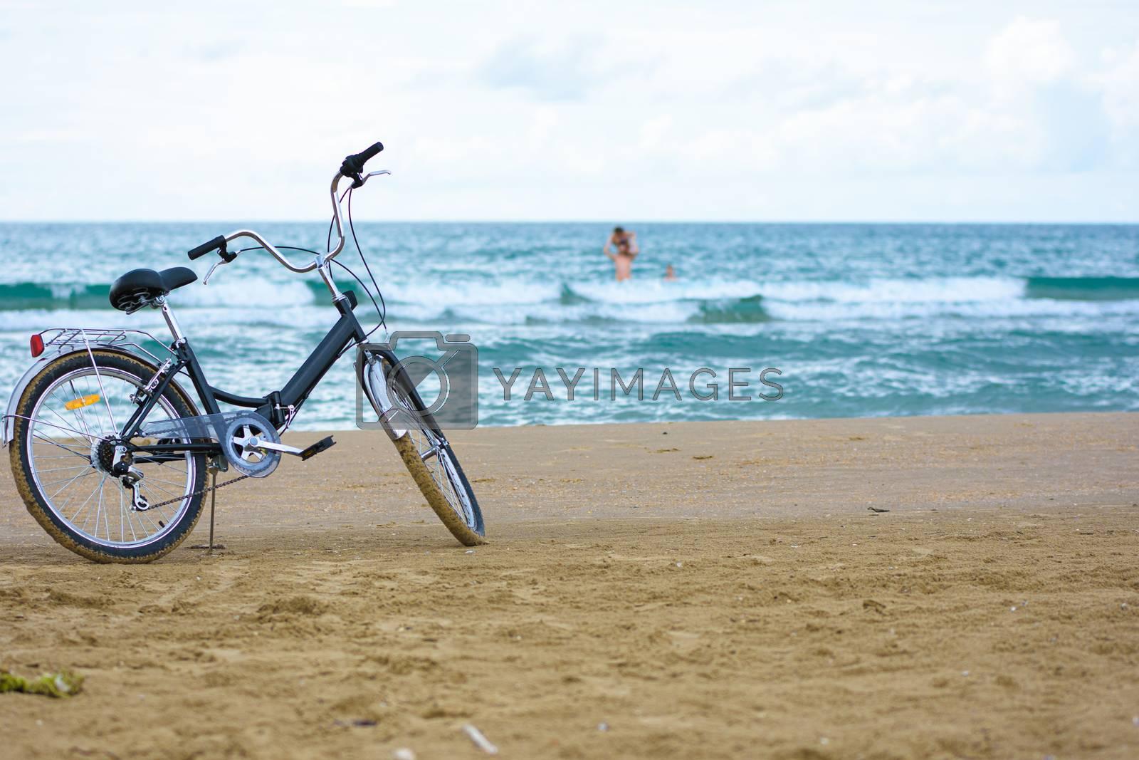 The bike stands on the sandy sea beach
