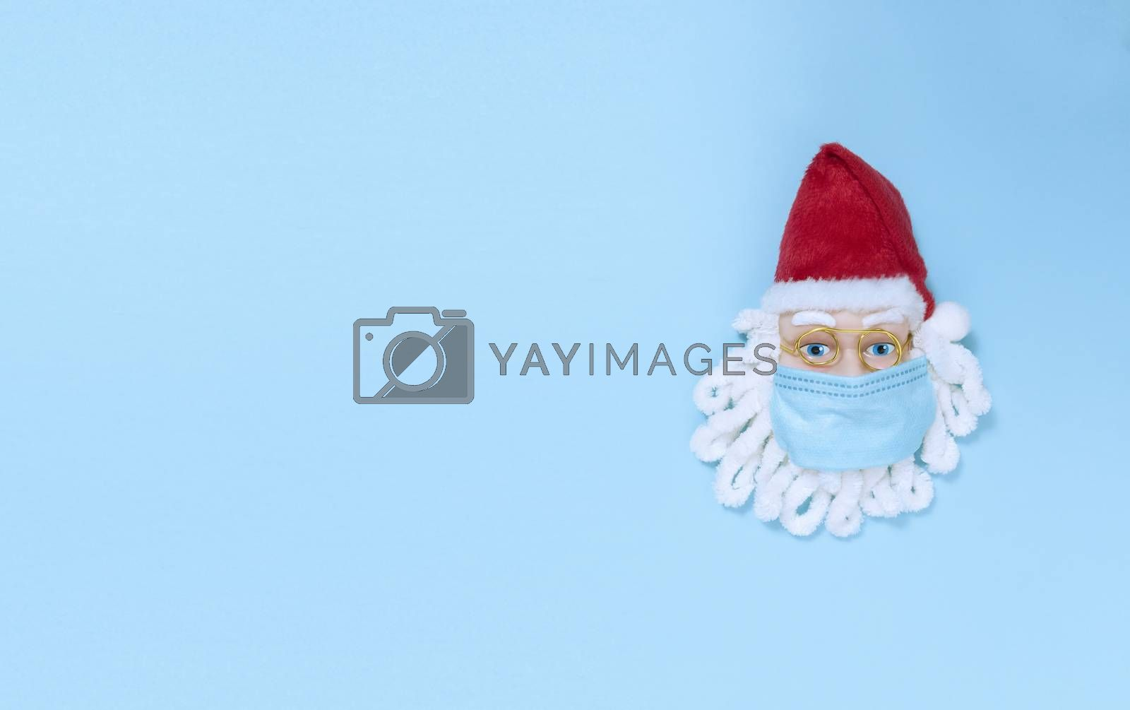 Santa Claus in medical mask on blue paper. Simple flat lay with copy space.