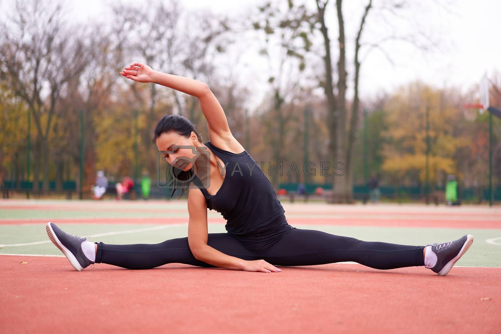 Happy girl doing fitness exercises outdoor on playground. Healthy lifestyle. Morning workout positive emotion smiling sportive people. one female training stretching