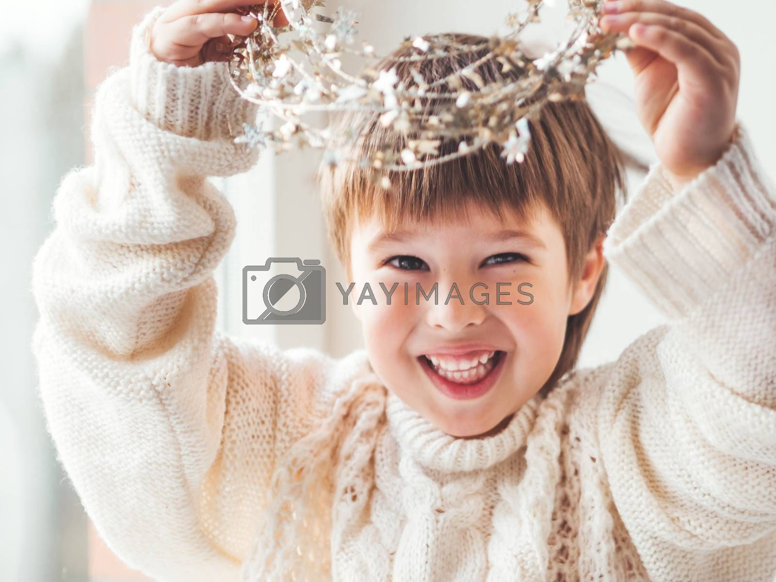 Kid with decorative star tinsel for Christmas tree. Boy in cable-knit oversized sweater. Cozy outfit for snuggle weather. Winter holiday spirit.New year.