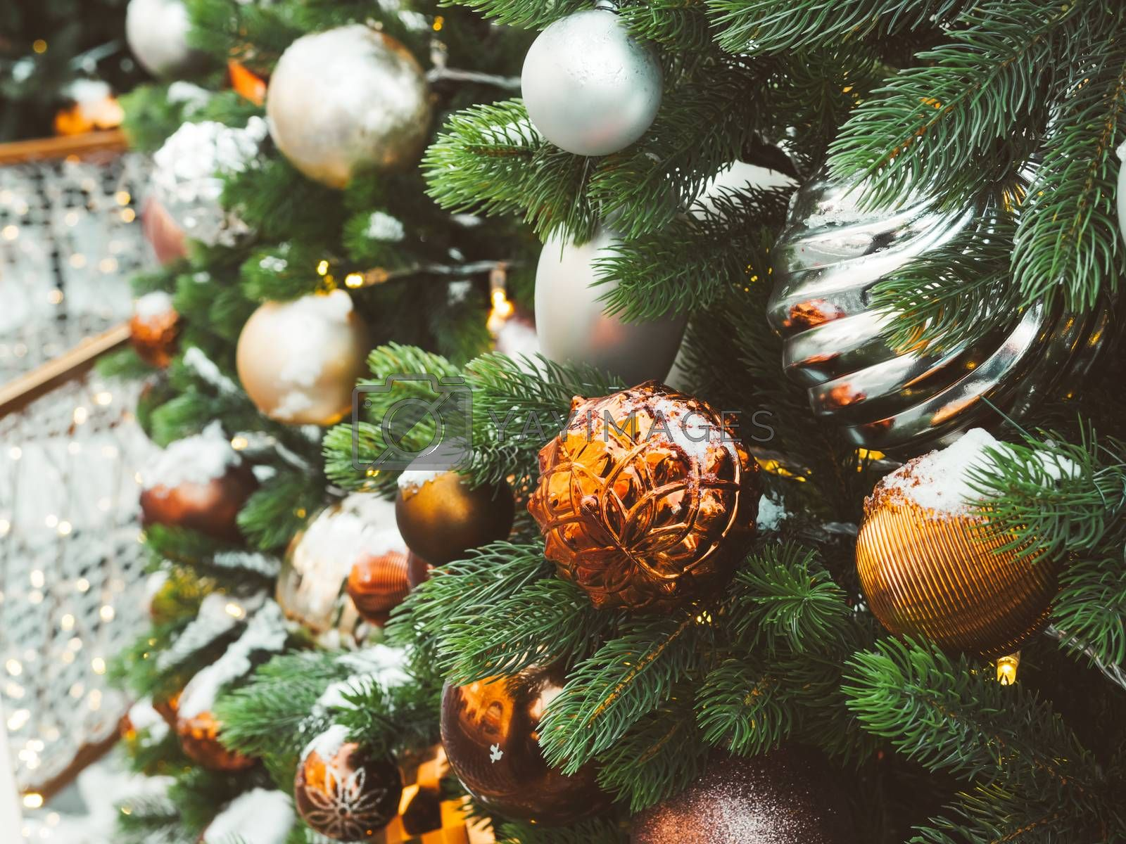 Christmas tree with silver and bronze balls. Outdoor decorations for New Year celebration.