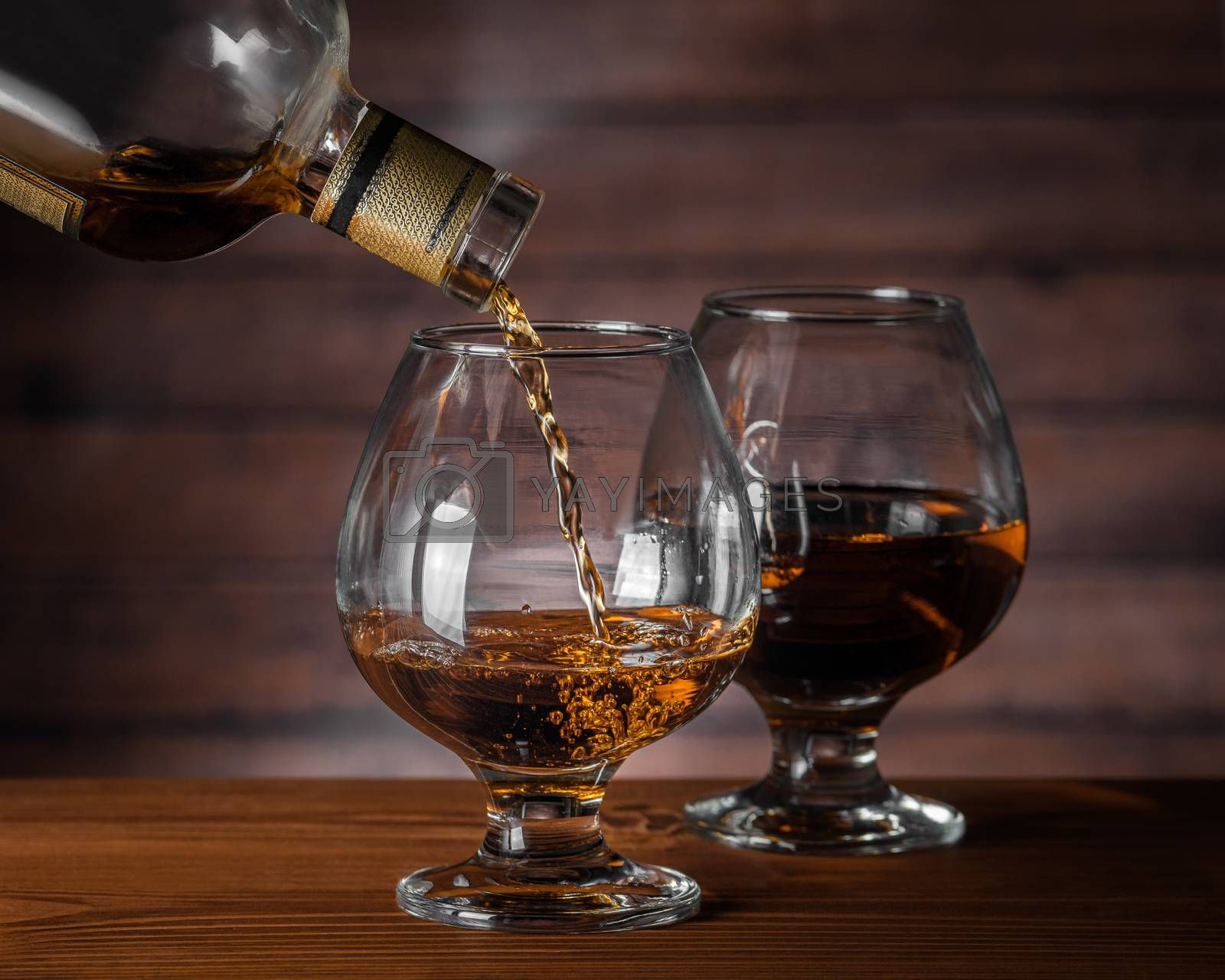 Royalty free image of Cognac is poured from a bottle by VladimirZubkov
