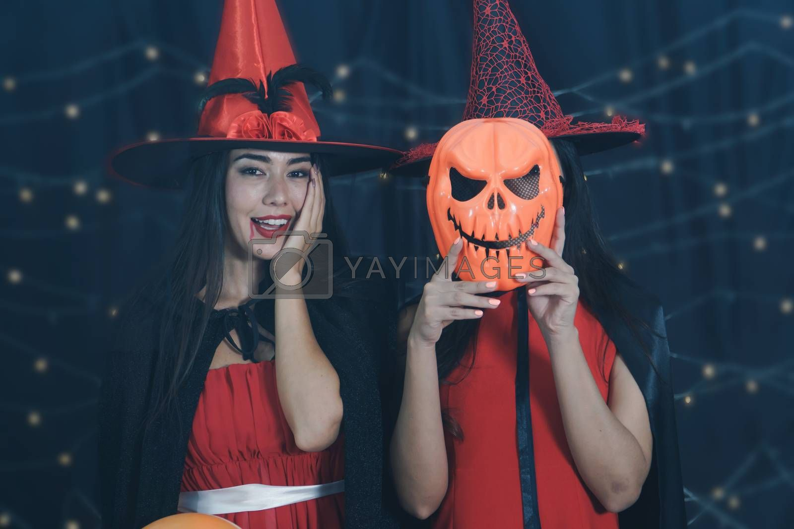 Beautiful Caucasian women and friends dressed up in Halloween witch costumes. Attractive young woman holding a carved pumpkin mask and Have fun at a party Halloween Celebration