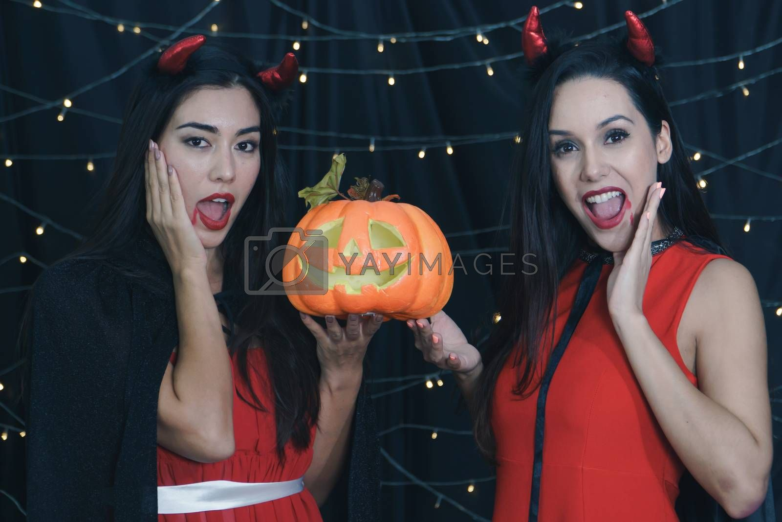 Beautiful Caucasian women and friends dressed up in Halloween witch costumes. Attractive young woman holding a carved pumpkin and Have fun at a party Halloween Celebration