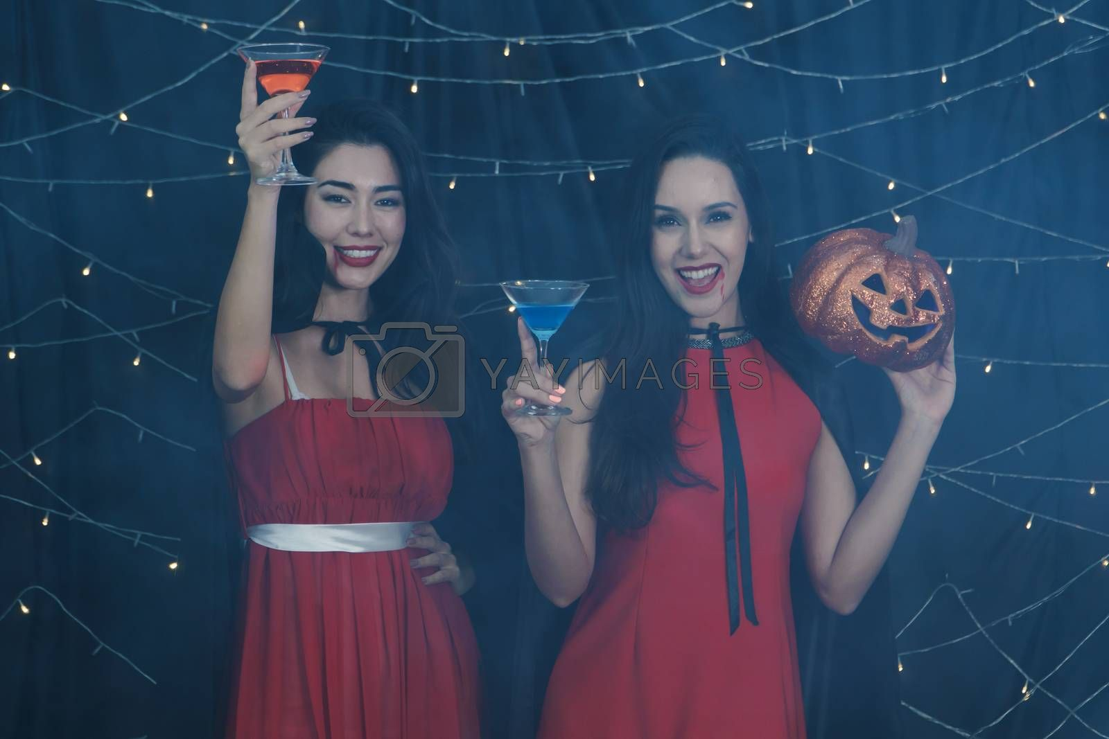 Beautiful Caucasian women and friends dressed up in Halloween witch costumes. Attractive young woman holding a pumpkin carving and drinking Cocktails. Have fun at a party  Halloween celebration