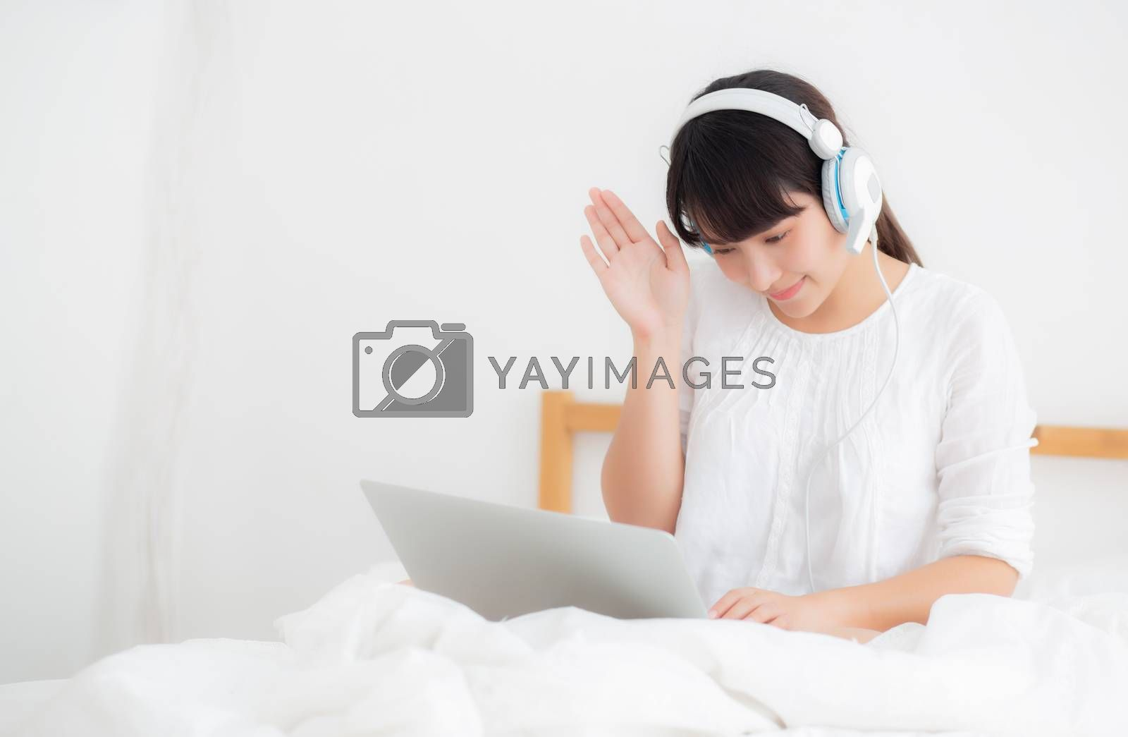 Beautiful young asia woman lying in bedroom using laptop computer showing video call chat at home, girl greet and listen and talking messenger, communication and lifestyle concept.