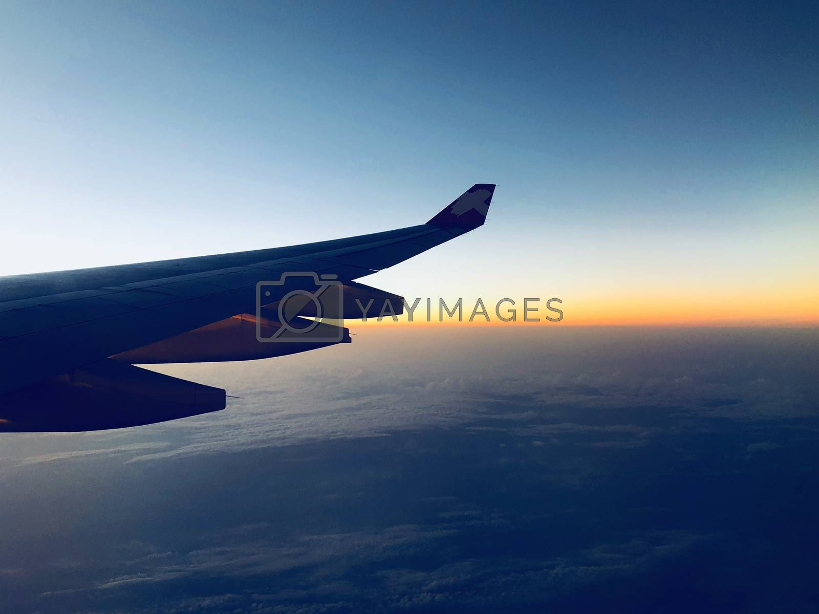 Sunrise on twilight sky, amazing view from the window plane.