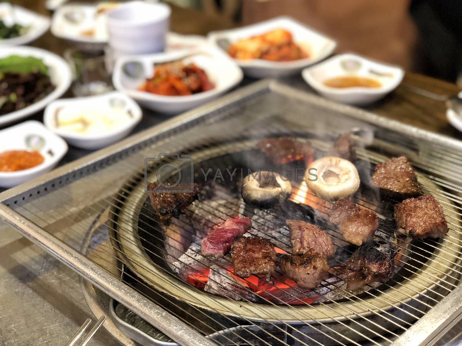 Grill meat on hot coals. This kind of food is a Korean or Japanese BBQ style.