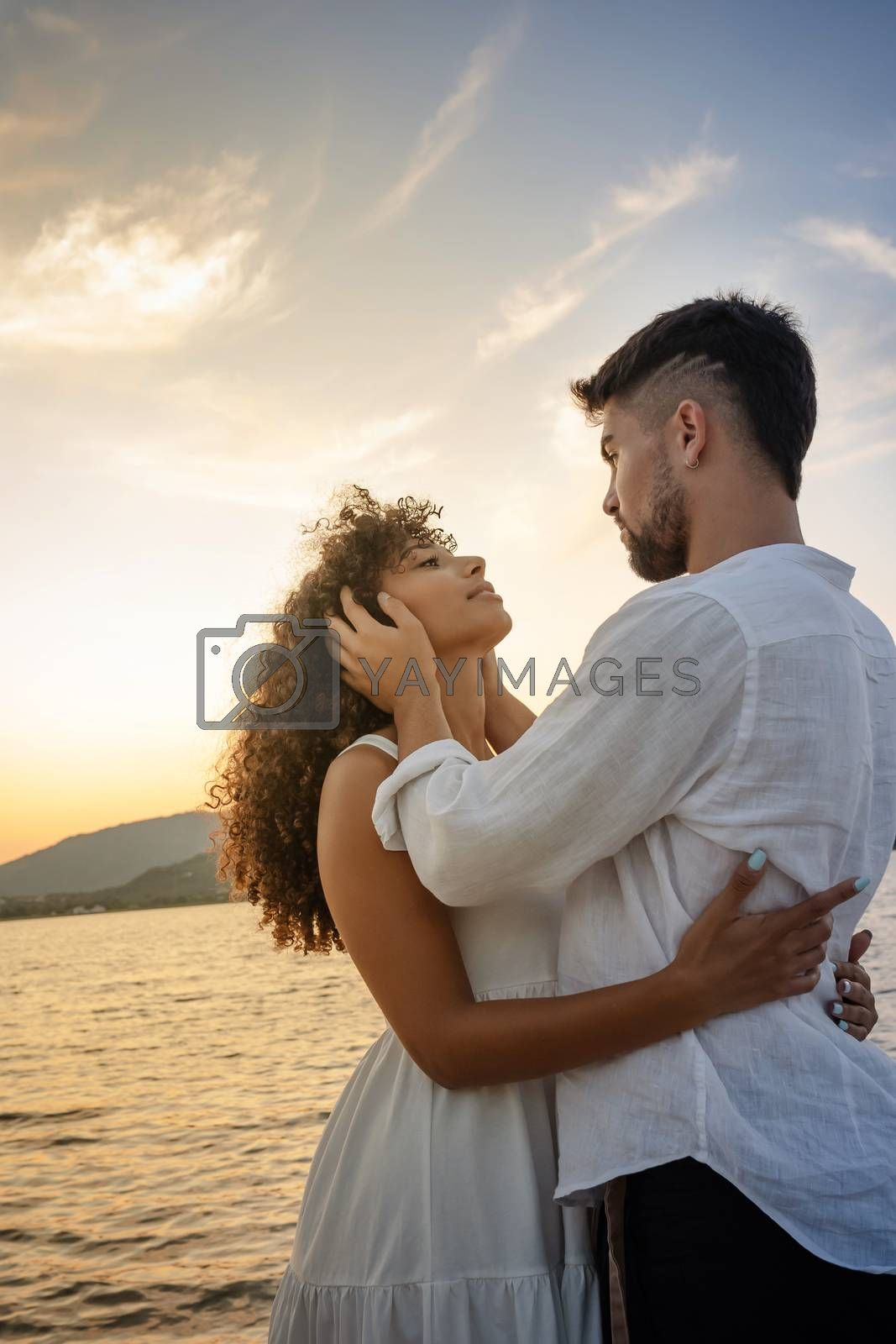 Royalty free image of Young attractive caucasian bearded man with modern haircut holds his black Hispanic girlfriend's head in his hands looking into her eyes while she hugs him - Multiracial couple romance scene at sunset by robbyfontanesi