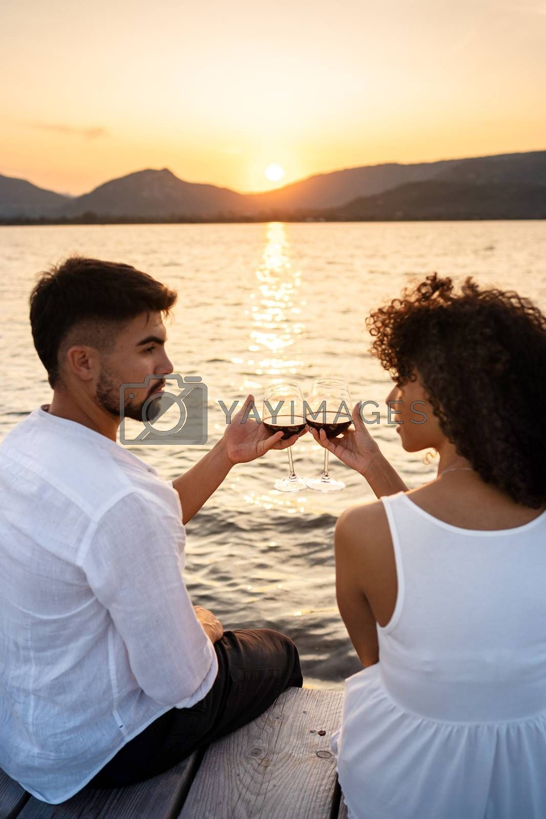 Royalty free image of Romance scene of multiracial couple sitting on a pier at sunset or dawn toasting with red wine looking each other in the eyes - Attractive man bonding with her Hispanic girlfriend - Focus on glasses by robbyfontanesi