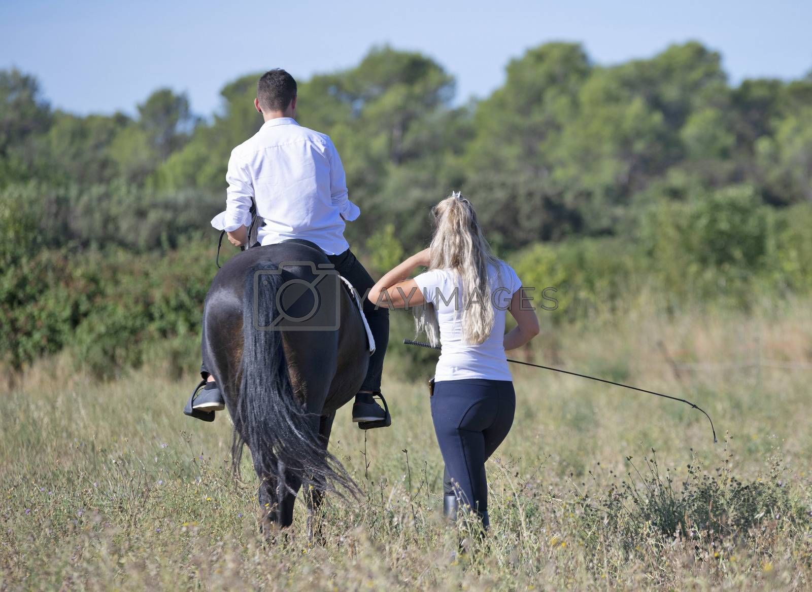 riding teenager are training her black horse