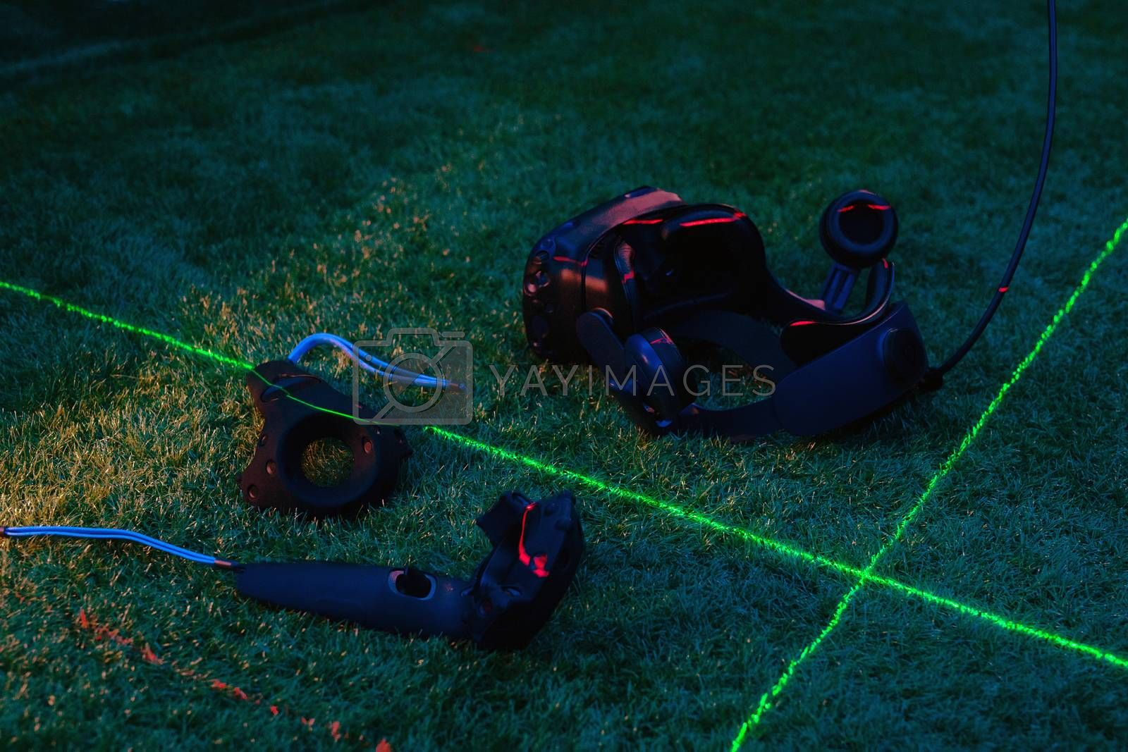 VR equipment set presented on green background goggles, scanners, two remote controllers in the light of green and red lasers