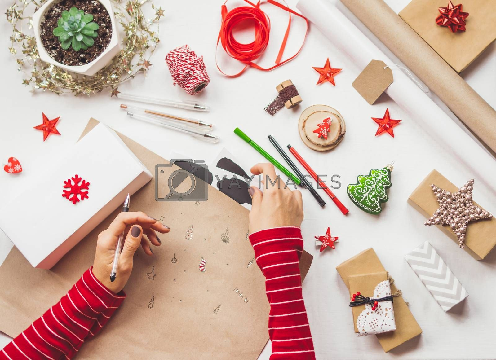 Top view on table with Christmas decorations. Left handed woman draws New Year symbols on craft paper and wraps presents. Flat lay.