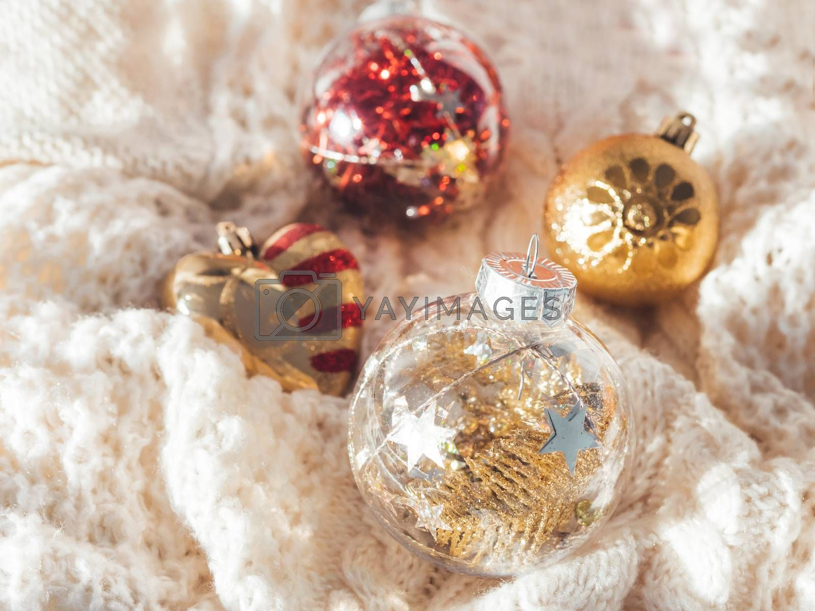 Decorative balls for Christmas tree on cable-knit sweater. Transparent sphere with red, golden spangles inside. Winter holiday spirit. New year celebration.