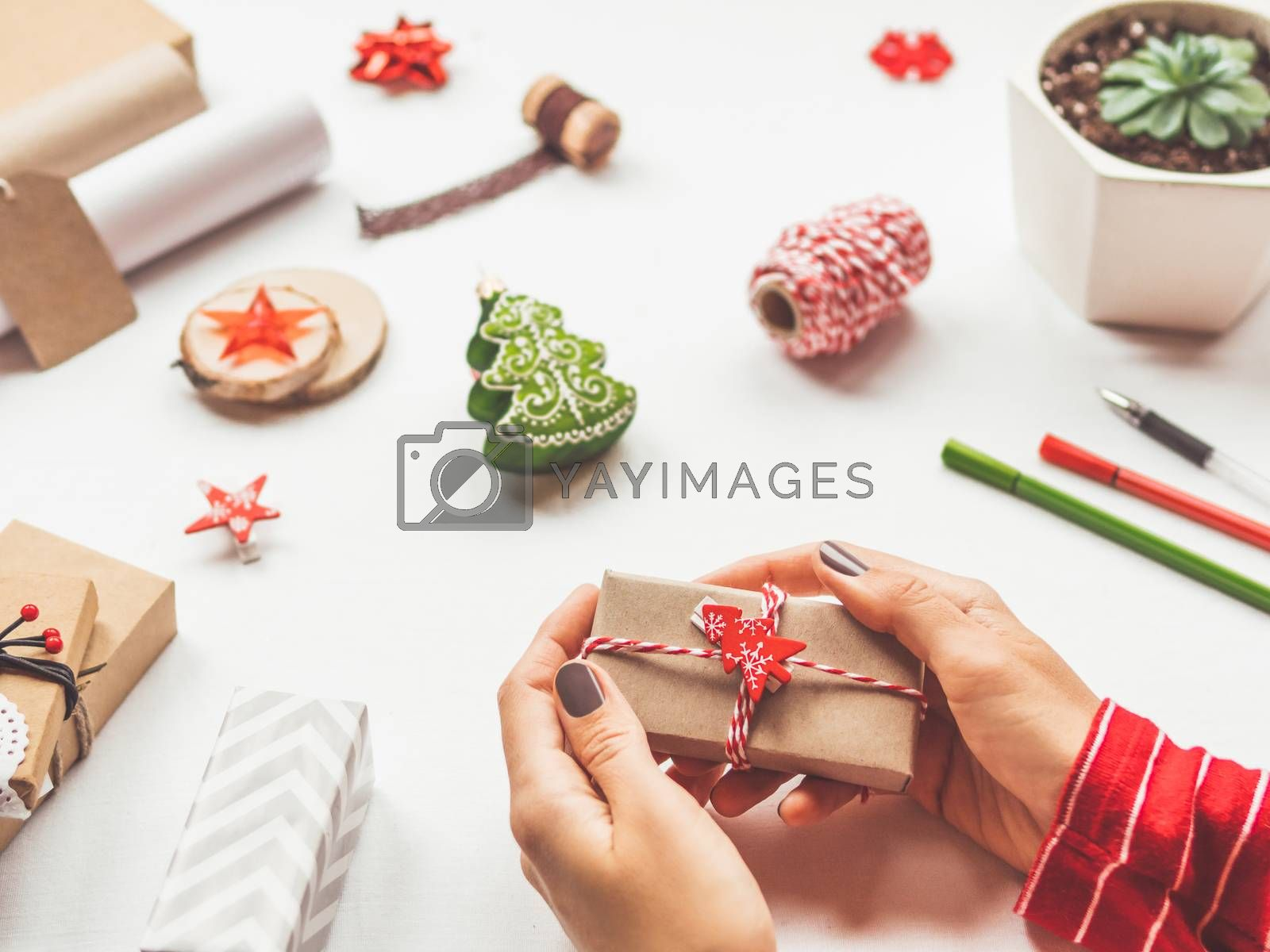 White table with Christmas decorations. Woman wraps New Year gift on craft paper. Winter holiday spirit.