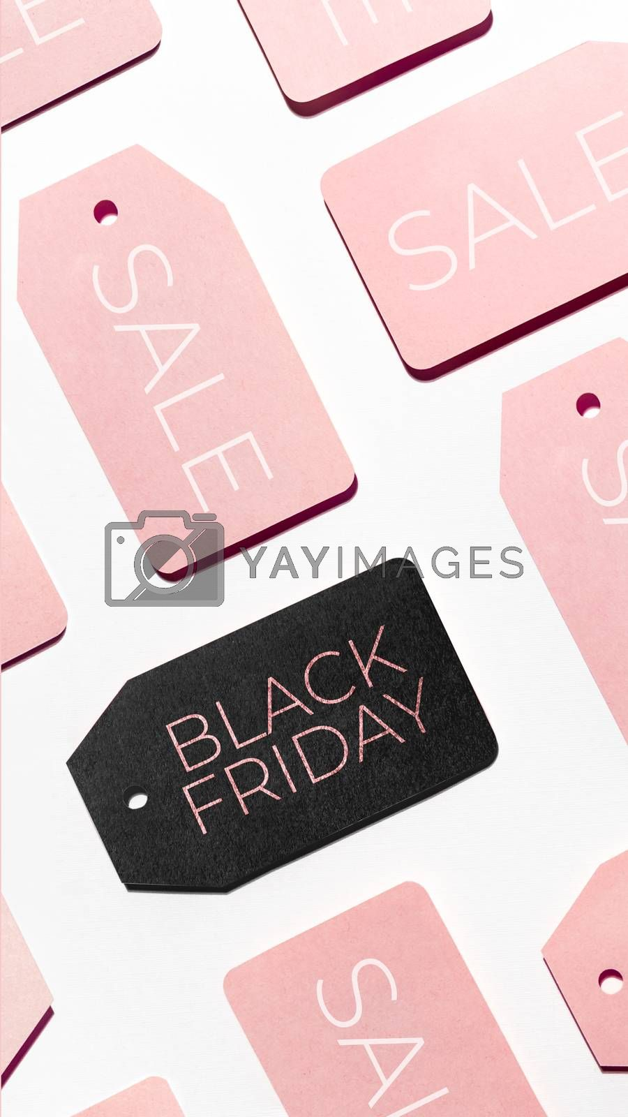 Top view on pattern of many pink and one black clothes tags on white background. Glamorous labels. Symbol of Black Friday sale and shopping. Flat lay.